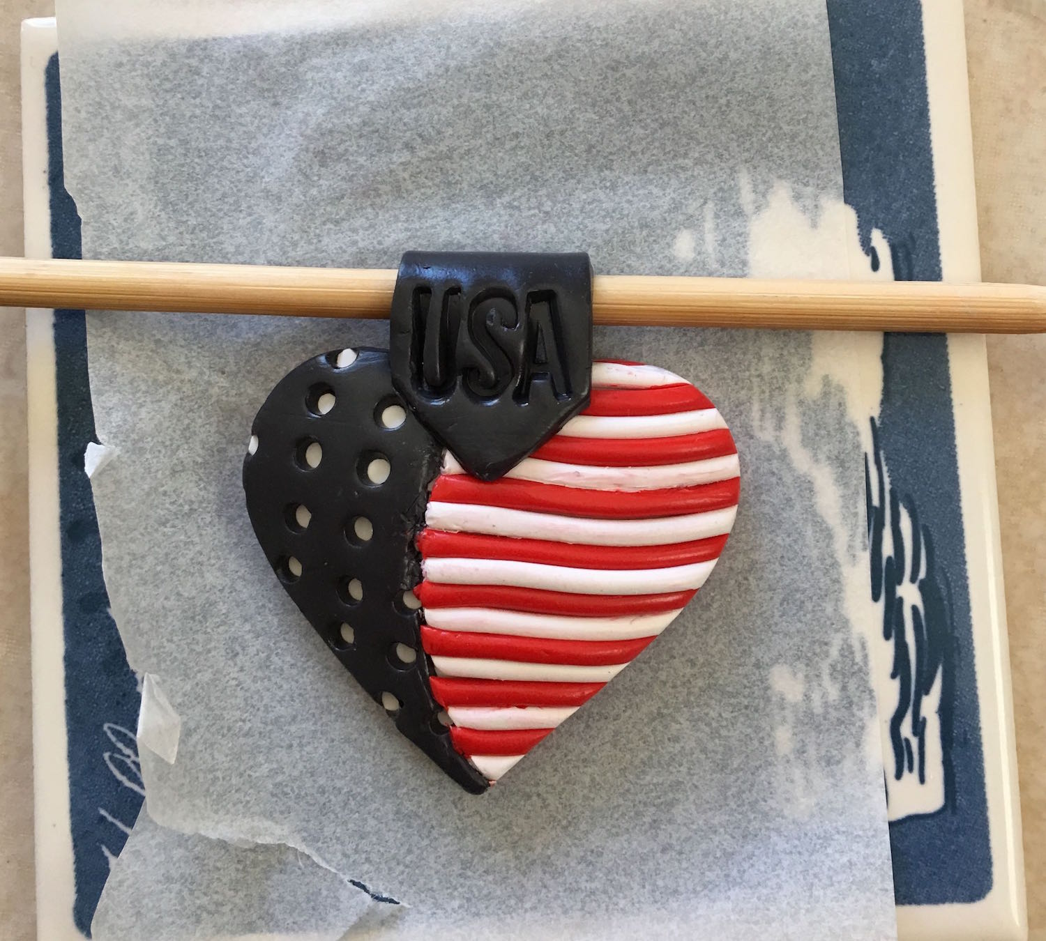 step 15 - Press the point of the clay to the center of the heart. Bring the rest of the strip to the back of the pendant and trim away the excess. Place a wood pick into the bail loop to hold the strip open while baking.