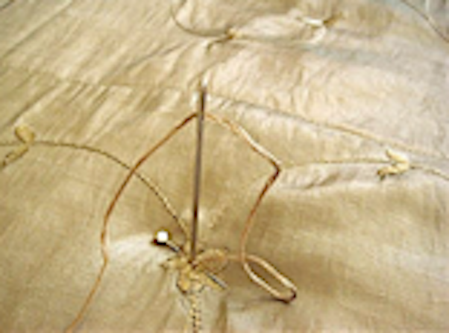 step 11 - Put the comforter on the bed. Thread a sharp needle with a large eye using the floss. Start making tufts by pushing the needle through the underside of the comforter, bringing it up through all layers. About 1/8 inch away from your exit point, push the needle back down to the underside.