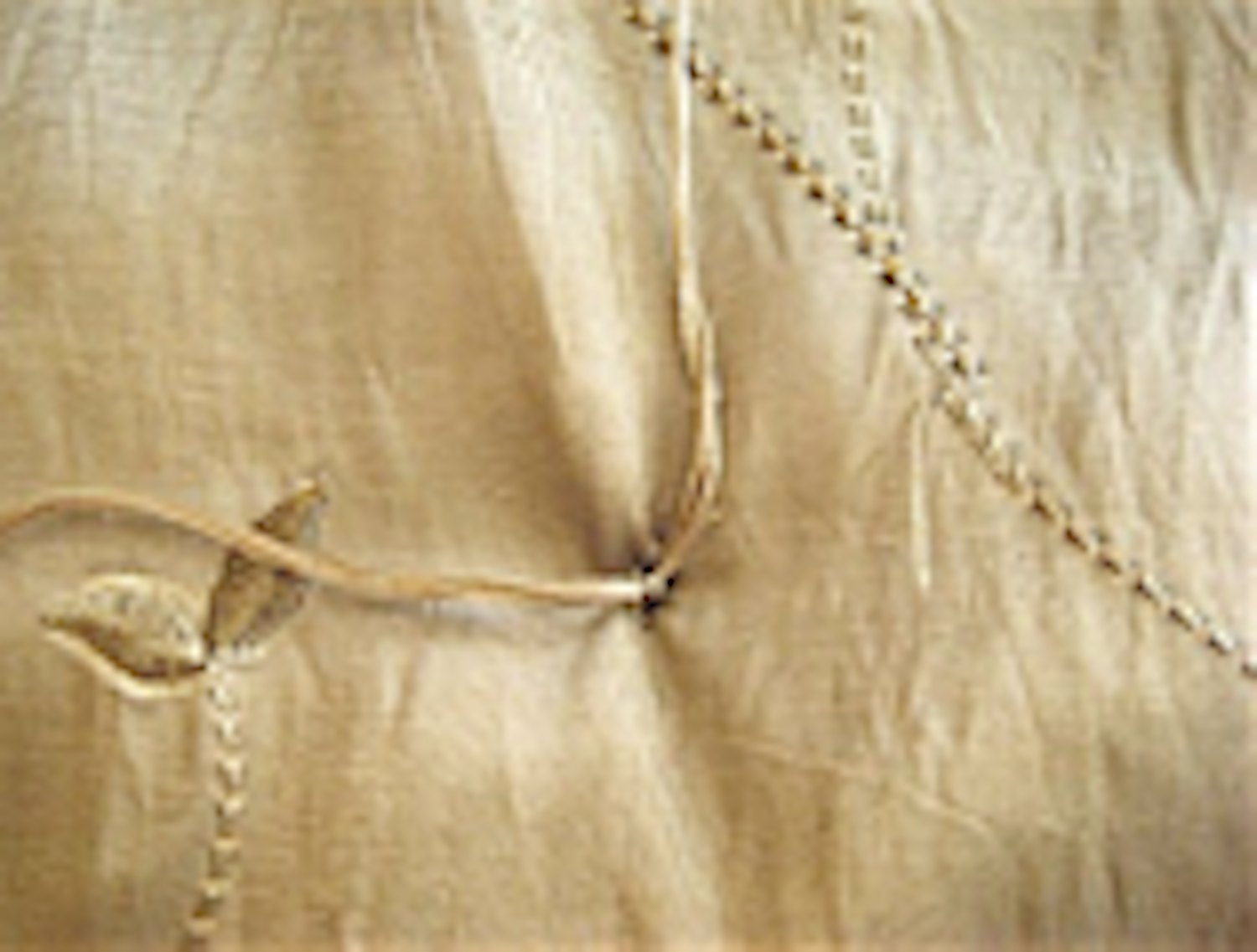 step 12 - Tie a triple knot in the two pieces of floss on the underside. Cut off excess floss close to the knot. Tuft at every marker of the comforter working from the center out, until all tufts are completed.