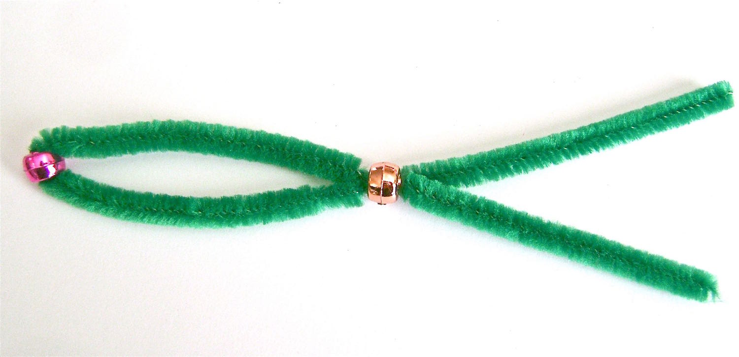 step 4 - Slide a bead into the center of a pipe cleaner.  Slip both ends of the pipe cleaner into a second bead.
