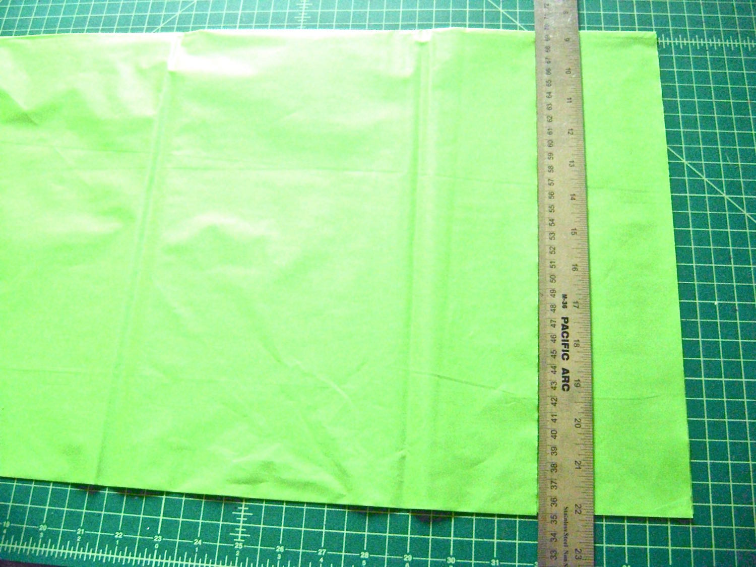 """step 3 - Remove the table cloth from the package and unfold it lengthwise. Do not open the width, leave it folded so you can cut several strips at once. Cut 3.50"""" wide strips across the length. You will need three of the green, yellow, and pink. Cut 21 to 24 of the white. How tightly you gather the strips will determine how many you will need. The individual strips will each measure3.5"""" x 54""""."""
