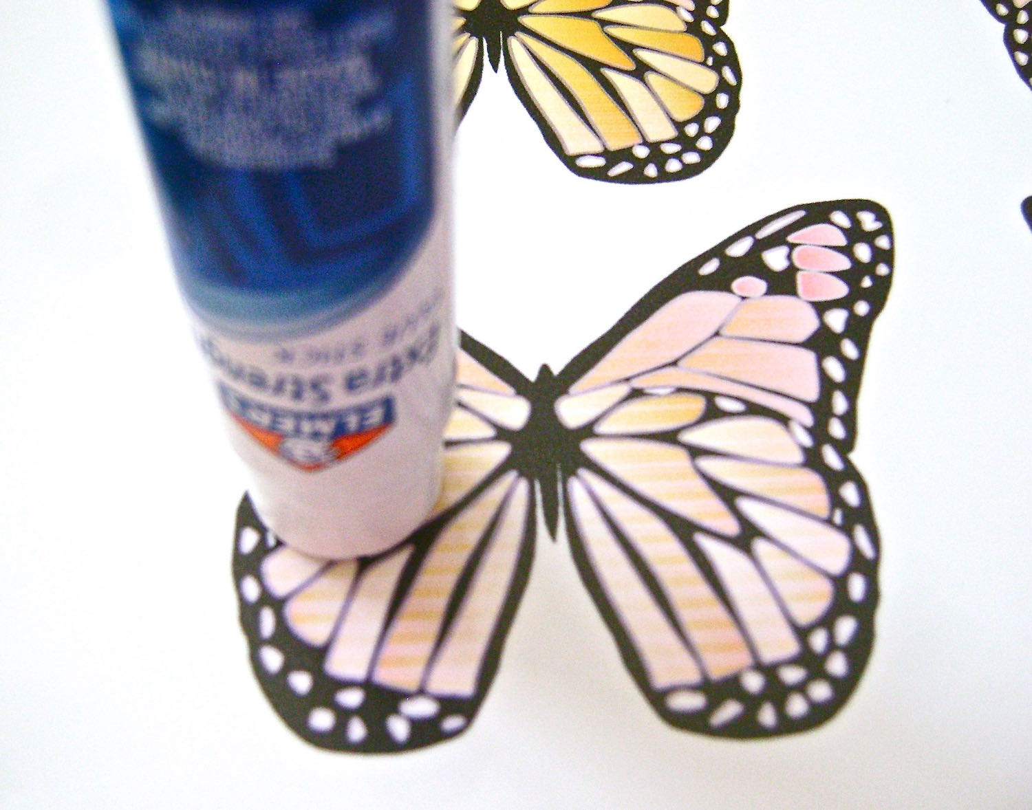 step 3 - Apply glue to the butterflies working on one at a time. Hold the glue stick flat against the printed image with light pressure. Work ina circular motion. Pressing down too hard on the glue stick will leave streaks of glue and lumps in what should be smooth wings.