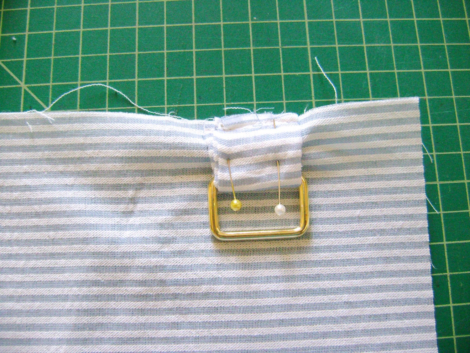"""step 4 - Fold pillow tabs in half with right sides together. Stitch on the long edge. Turn right side out. Slip on the metal rectangle and bring the tab ends together. Pin the tab ends to the 16"""" side of the pillow fabric, 2"""" in from the corner."""