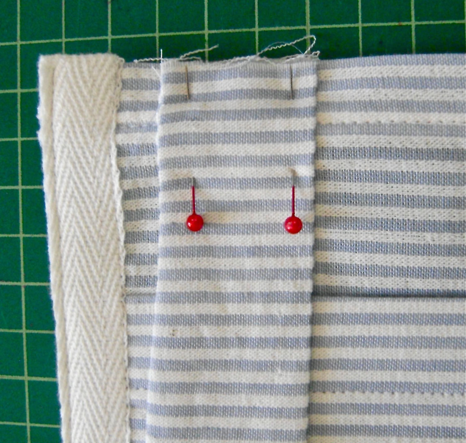 """step 14 - Position straps on the upper front and back of the pocket back, one directly behind the other, one inch away from the tape. Stitch the straps 5/8"""" from the raw edges."""