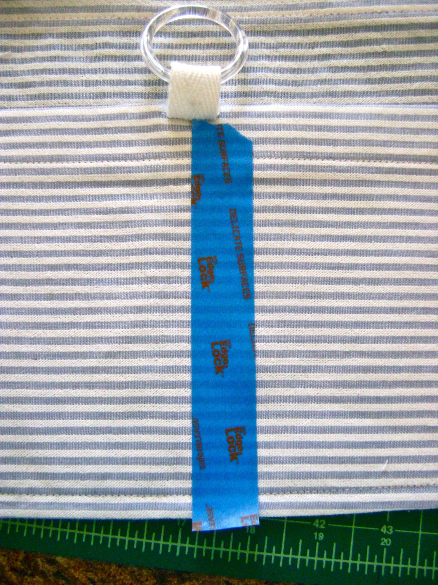 step 18 - Slip a piece of cotton tape through the plastic ring. Sew the tape to the top center of the pocket with the raw edges inside. Mark the vertical center of the pocket with tape and stitch along the tape edge from the bottomup to the tape to create a divided pocket.