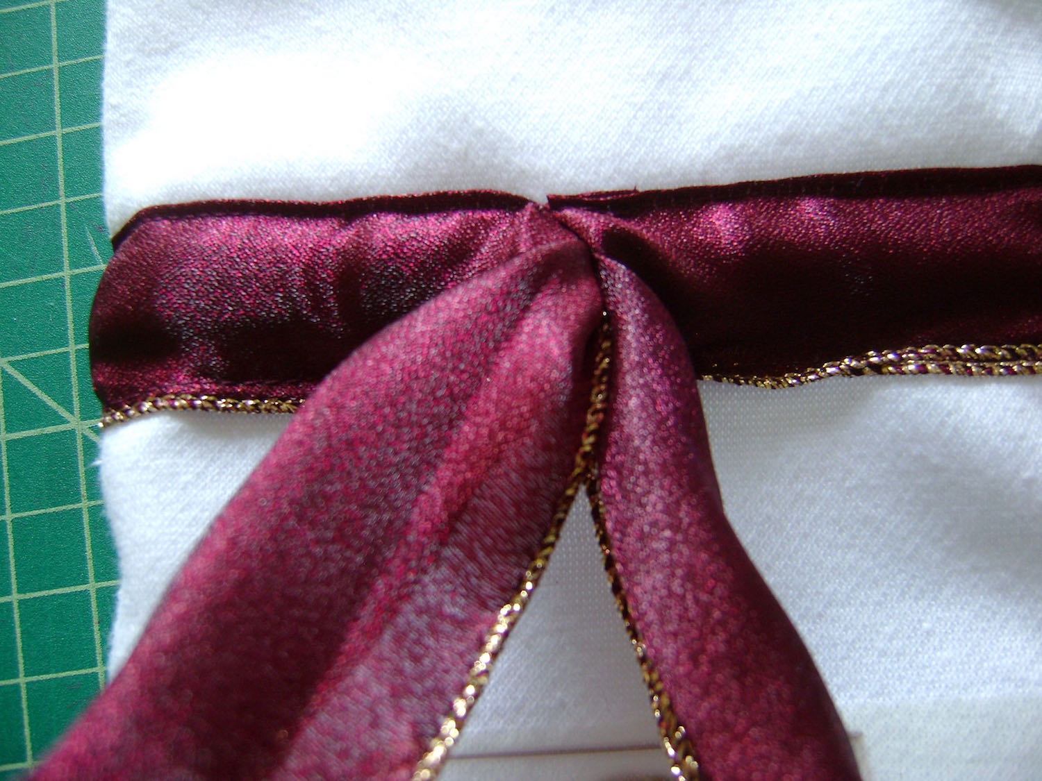 step 12 - Bring the safety pin out the center front. Put the bottle in the bag and tie the two ribbons together then into a bow. Cut off excess ribbon.