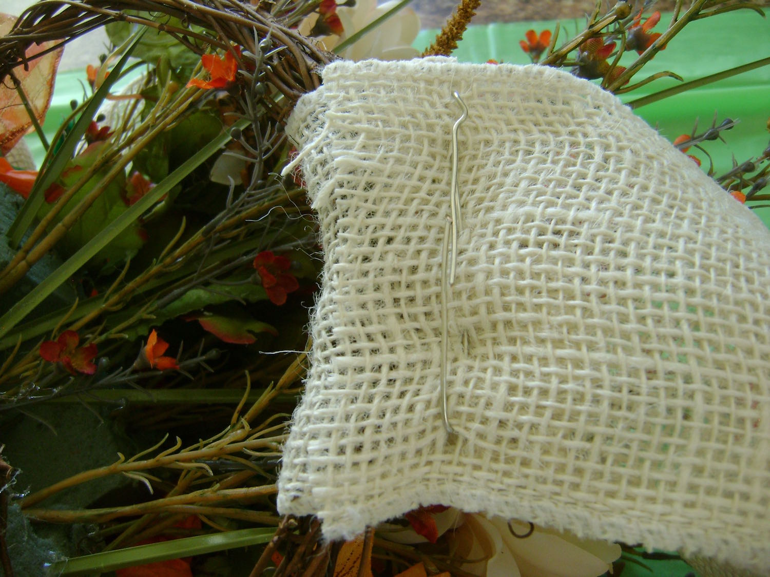 step 11 - If you prefer to hang your basket from a ribbon, double the length you need and cut a piece from the burlap. Fold the ribbon in half with the basket handle in between.Weave heavy wire in and out of the overlapped ends of the burlap to secure them together.
