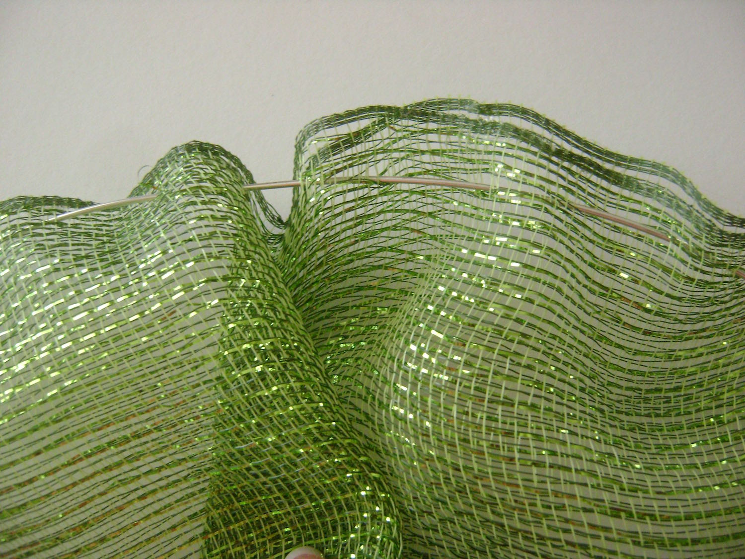 """step 5 - The Mesh Ruffle   Cut a strip of mesh 36"""" long. Fold it in half on the long side and hot glue the edges together.   Cut a length of wire 36"""" long. Slip the wire in and out of the glued side of the mesh at one inch intervals, about .50"""" from the edge."""