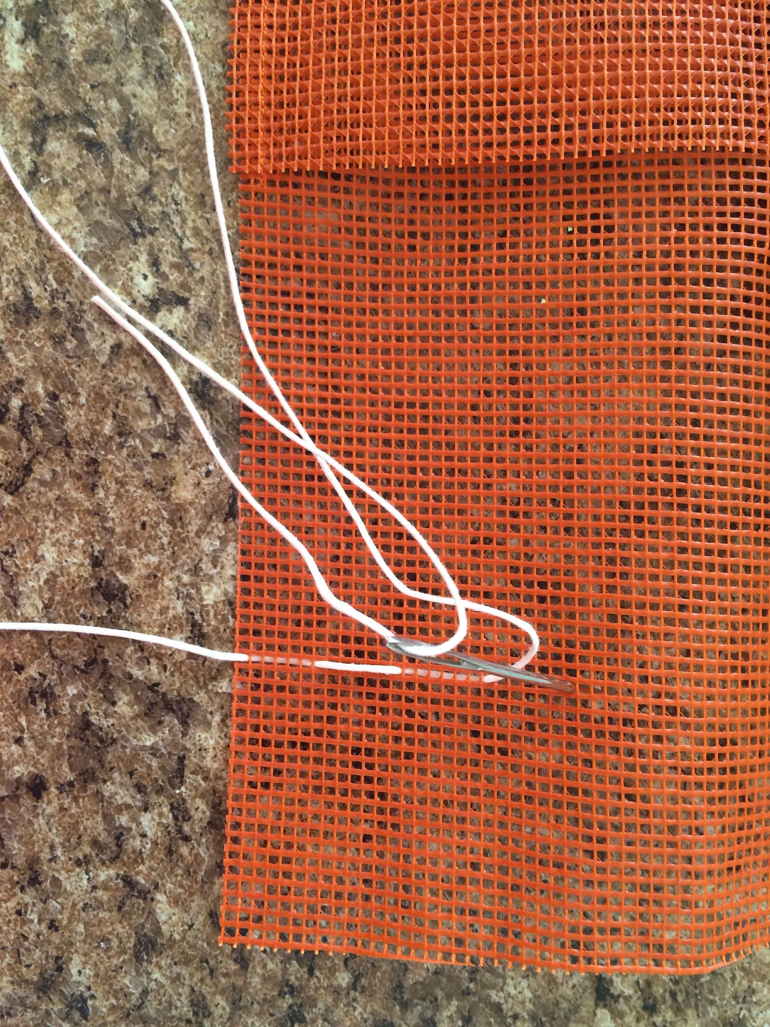 "step 5 - Measure your tallest tool and mark that many inches from the bottom with a pin.  Thread a large darning needle with 24"" of cotton cord and weave it in and out of the mesh every half inch across the length of the mesh."
