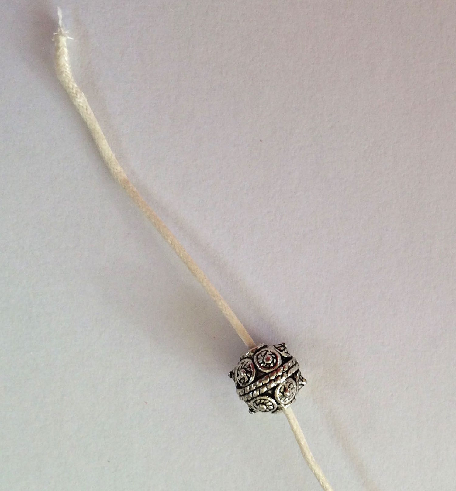step 6 - Attach a decorative bead to the cord ends then tie a double knot.  The beads will prevent the cord from slipping out of the mesh.