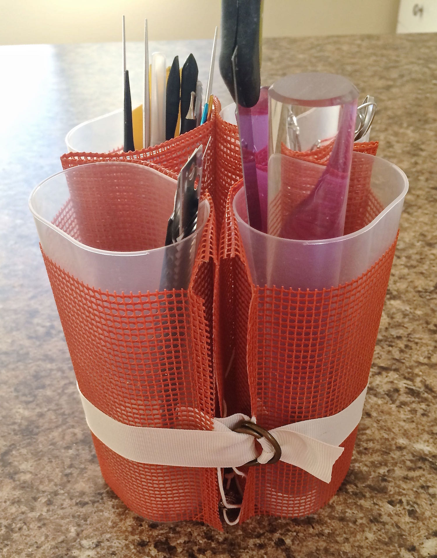 "step 9 - To group the containers, wrap the ribbon around them then secure the end in the ""D"" rings."