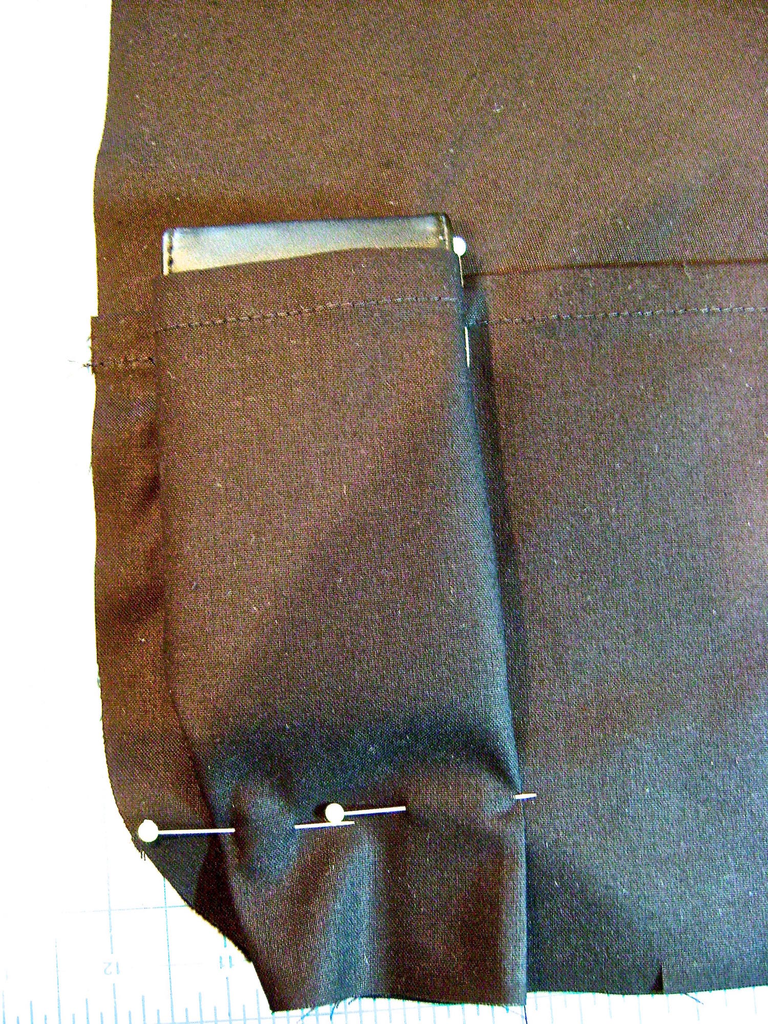 step 5 - Position your first item.  Drape the fabric over it and pin the pocket to the lining on the right side of this space.  Don't make it too snug.