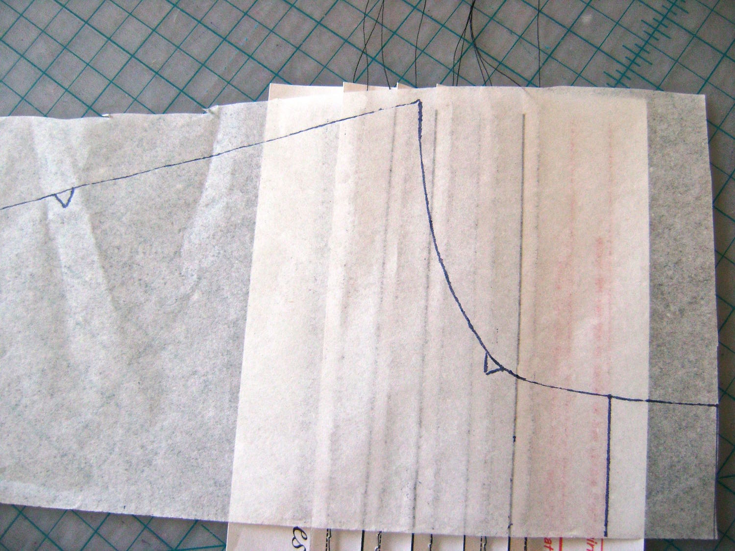 step 5 - Position your transparent paper with the traced neck edge, on top of the pleated template, matching the center lines.