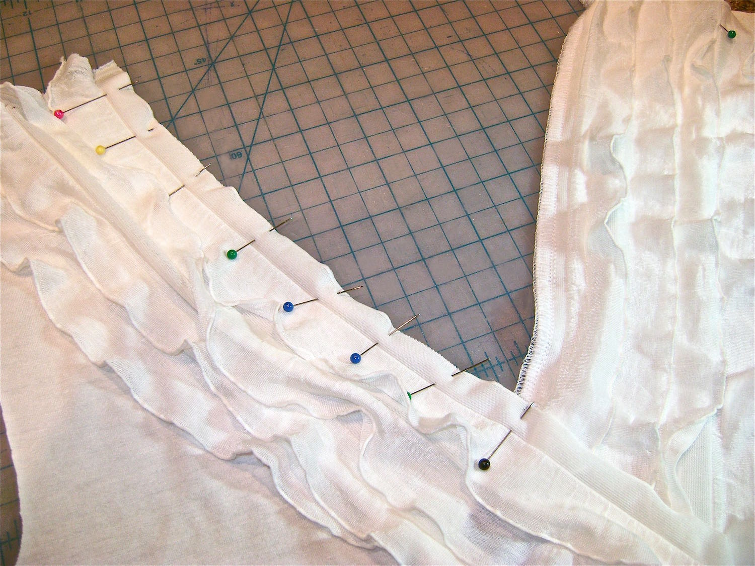 "step 9 - Pin the right side ruffle strip to right side of shirt front.   Follow steps 5 & 6.  At the end of the stitching, cut a little less than a ½"" slit in the flat margin which will allow it to be turned under."