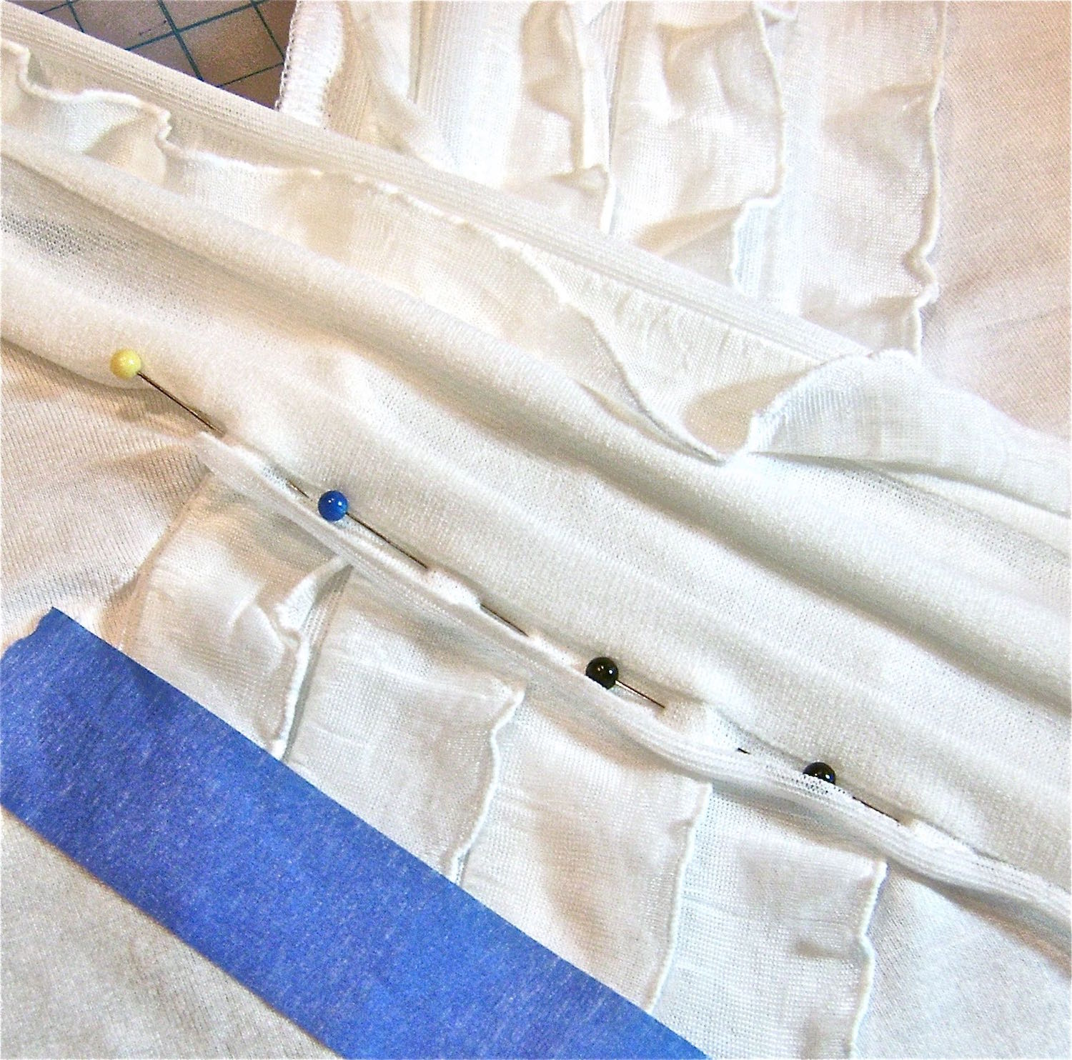step 10 - With the right side of ruffles to the right side of the shirt, sew the remainder of the left ruffle strip to the shirt, from the slit, over the left ruffles and all the way to the hemline. Remove the tape on the left ruffle strip and trim excess.