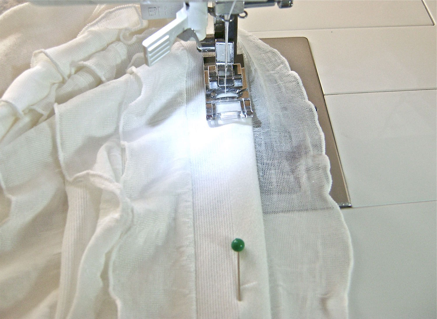 step 14 - Sew the front neck edges down by sewing underneath the first row of ruffles. The stitching will be hidden when the ruffle is in place. Top stitch the back neckband.