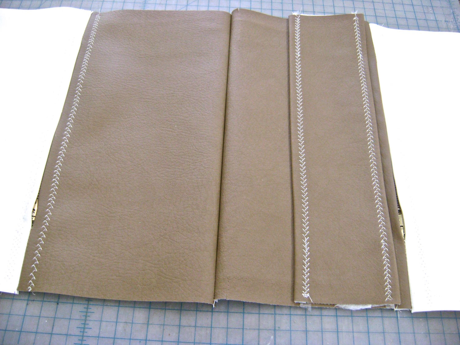 """step 9 - Join the bag front and back sections by sewing a seam at the bottom. Position the sleeve .50"""" below the pocket zipper. Tape or pin in place."""