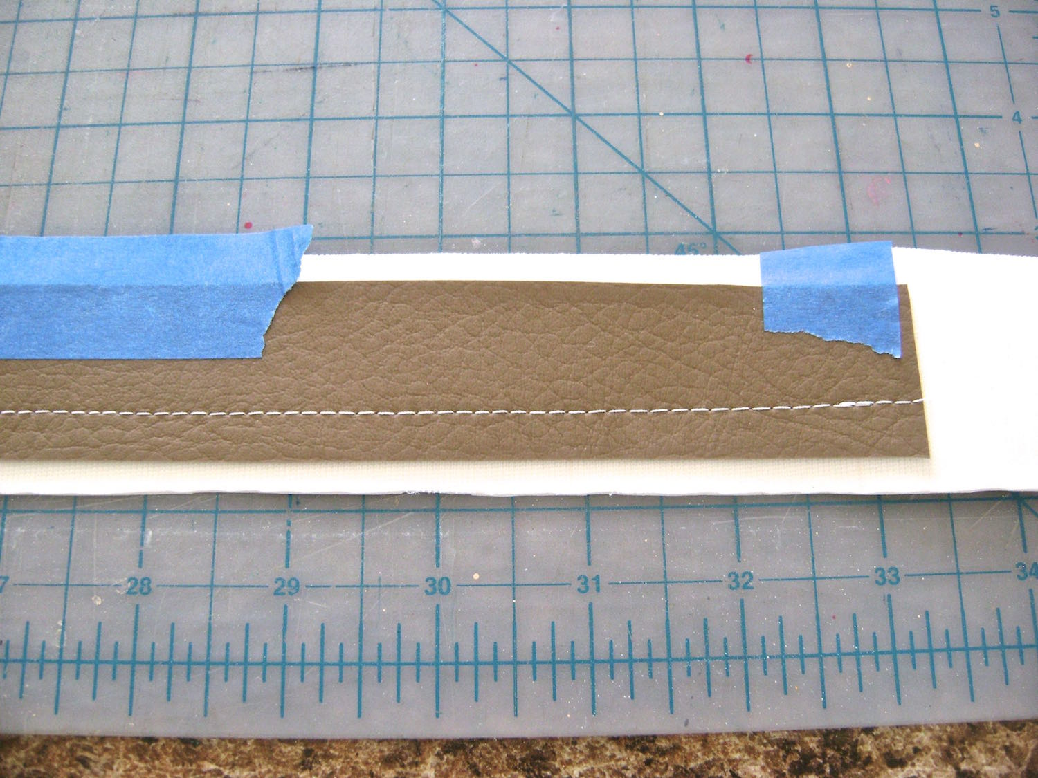"""step 18 - To create straps, tape the chestnut strap to the white strap with wrong sides together. Topstitch one edge. Topstitch again 5/8"""" from the first stitching. Trim both long edges to 1/4"""" from stitching. Trim the short edges even."""