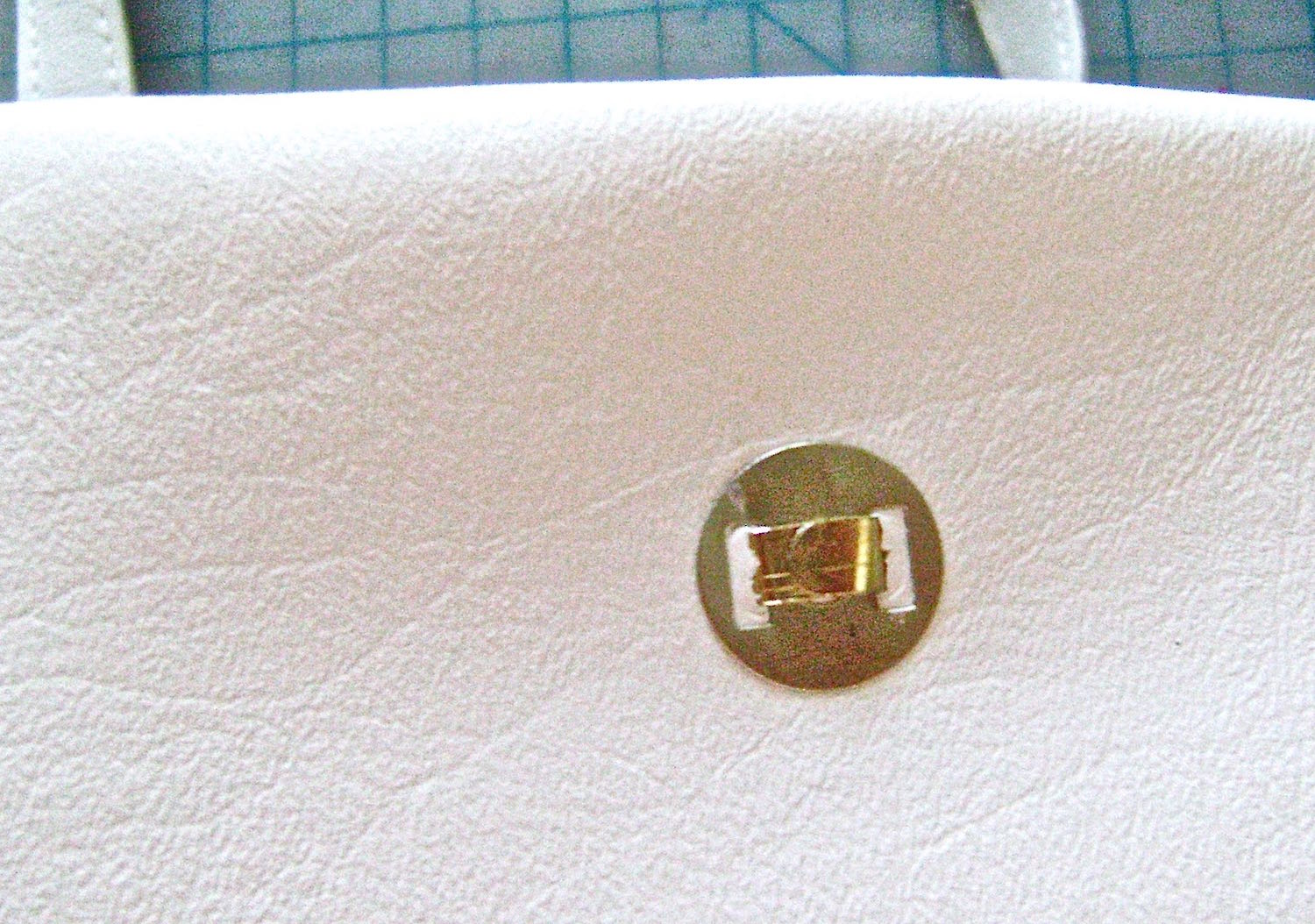 step 20 - Attach magnetic clasps to the center of facings on front and back of bag. Push the prongs through the facing and the white vinyl sections with the folded prongs on the outside of the bag.