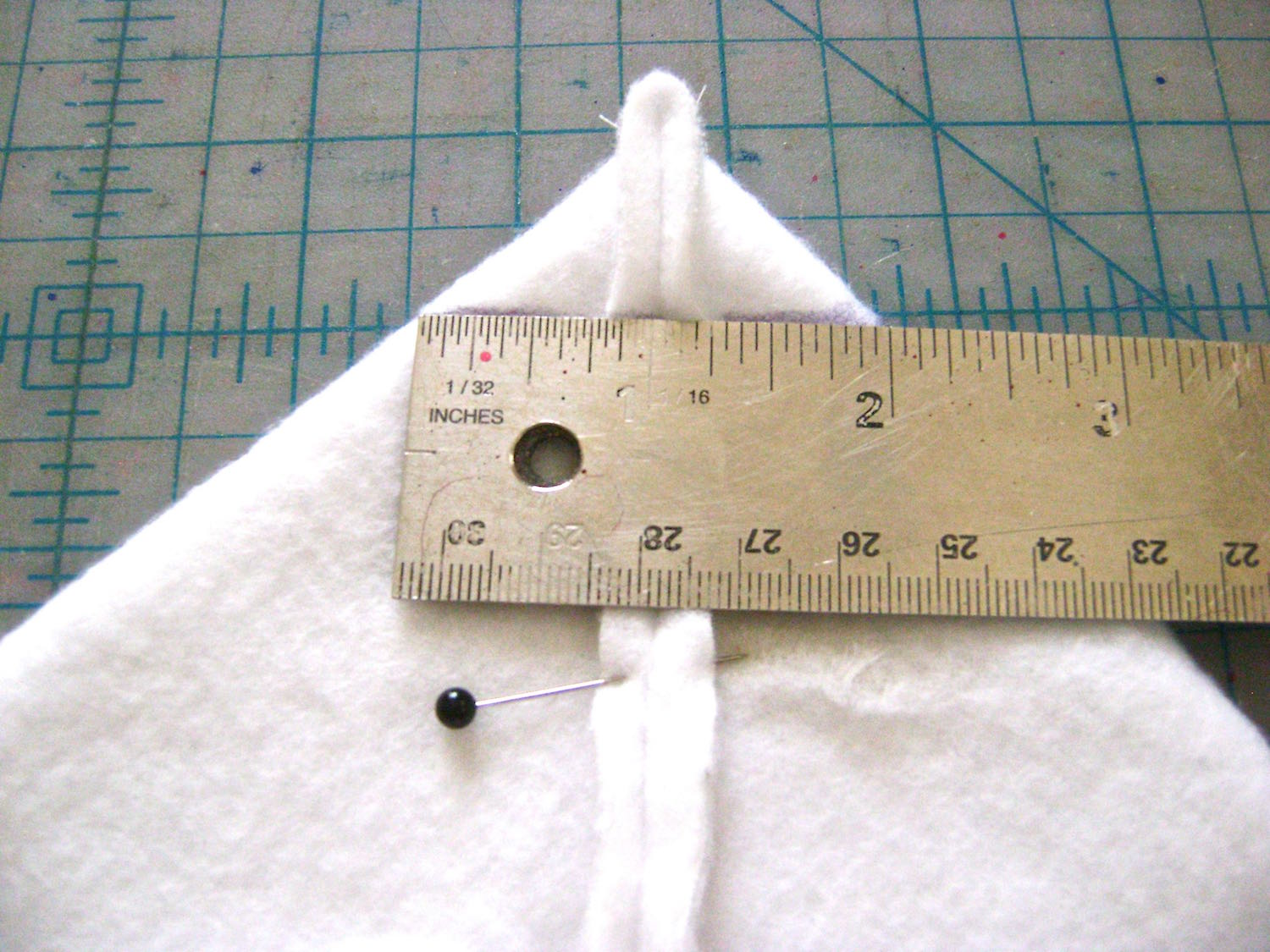 """step 16 - Sew the sides of the padding and lining. They are constructed in the same way. Sew the bottom seam leaving a 7"""" center opening in each. Lay the bottom seam against the side seam of the left and right bottom corners. Pin the seams together to create a triangle. Mark a line across the triangle to measure 2"""" across. There should be one inch to the left and right of the seam. Sew on the line to create the squared bottom corners of the bag."""