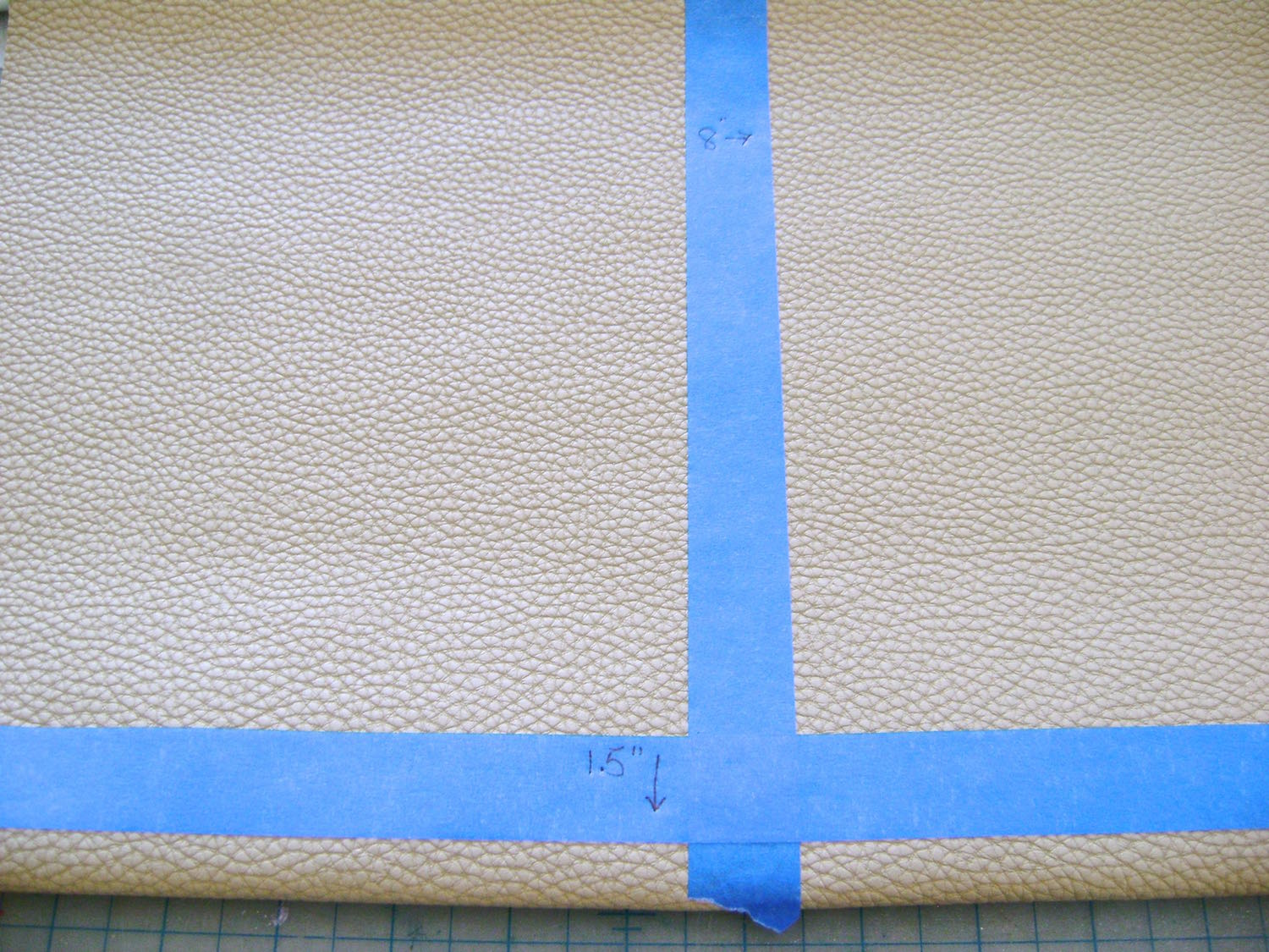 """step 5 - Use painters tape to mark the vertical center of the 16"""" vinyl as well as the horizontal line at the 1.50"""" mark."""