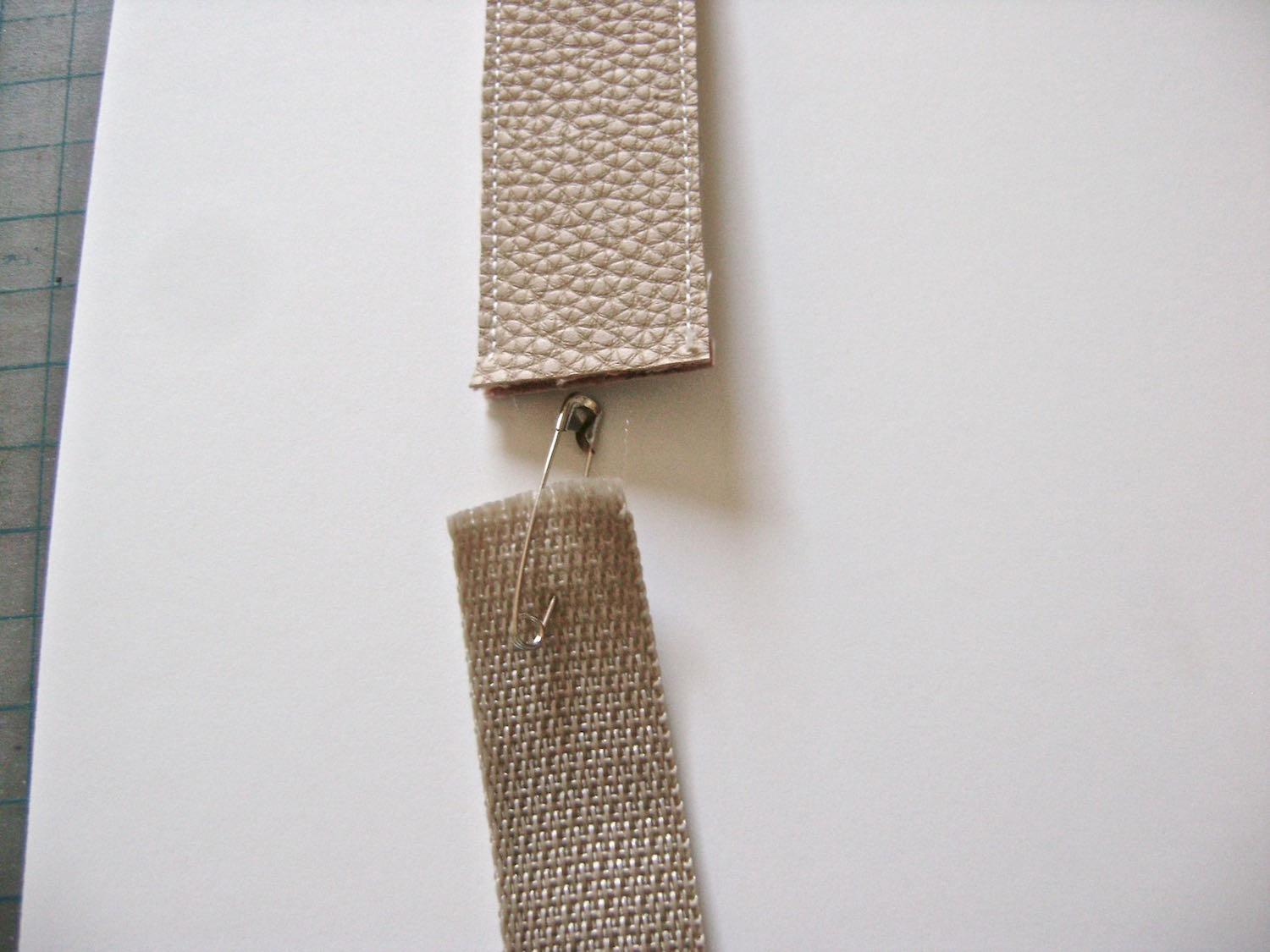 """step 20 - Place a safety pin on one end of the strap cord and thread it through the strap. It should be 1.5"""" shorter than the vinyl strap on each end ( a total of 3"""" shorter than the total length of the strap)."""