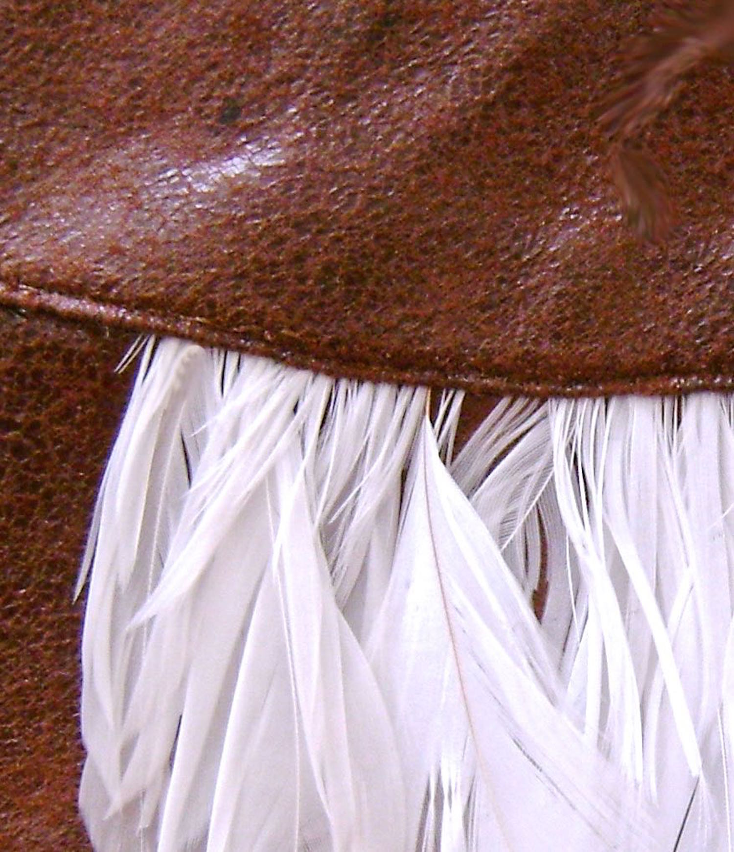 step 6 - Topstitch the cover to the front piece close to the curve and across the feathers.  Attach nail heads to the sides of the feathers to complete the owl design.