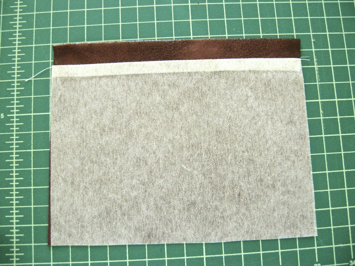"step 16 - Turn the pocket pieces wrong sides together.  Create a .50"" hem at the top of the pocket.  Cut off the .50"" excess interfacing and fuse the pocket pieces."