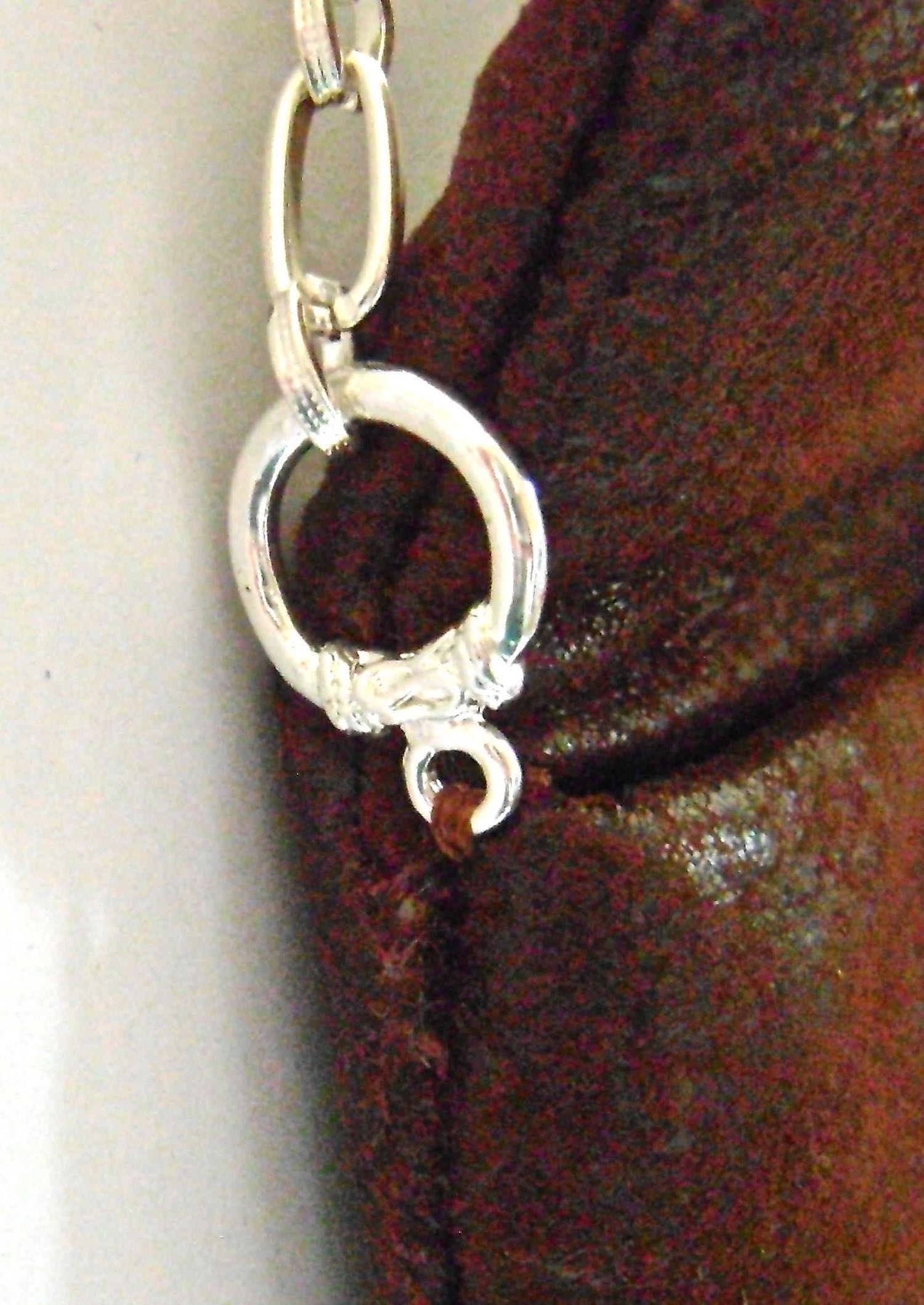 step 30 - Hand sew the round end of a toggle clasp to each top side edge of the purse.  Attach chain to the clasp.