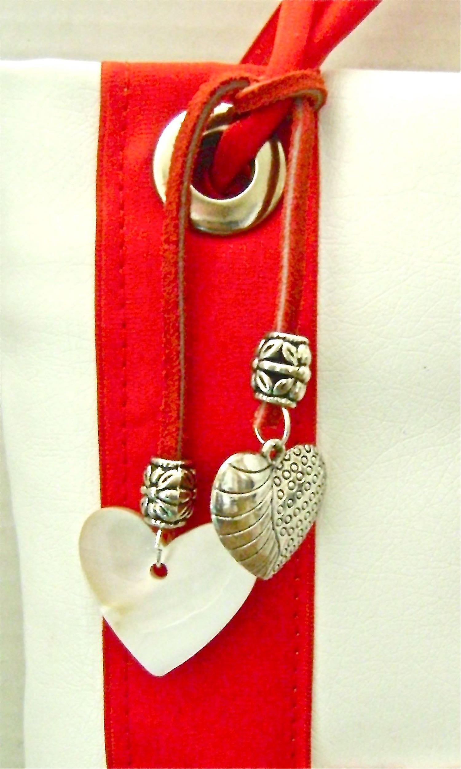 "step 19 - Poke holes in the ends of a 7"" strip of rawhide cord with a sharp needle.  Attach decorative silver beads and attach heart charms with jump rings. Tie the cord around the ribbon."