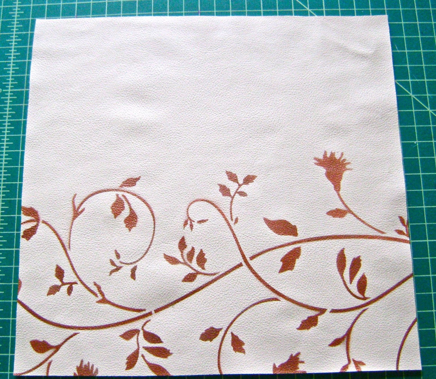 "step 3 - Apply adhesive to the back side of the stencil.  Apply it sticky side down to the front vinyl piece so that the floral design begins about 4.75"" from the top of the piece."
