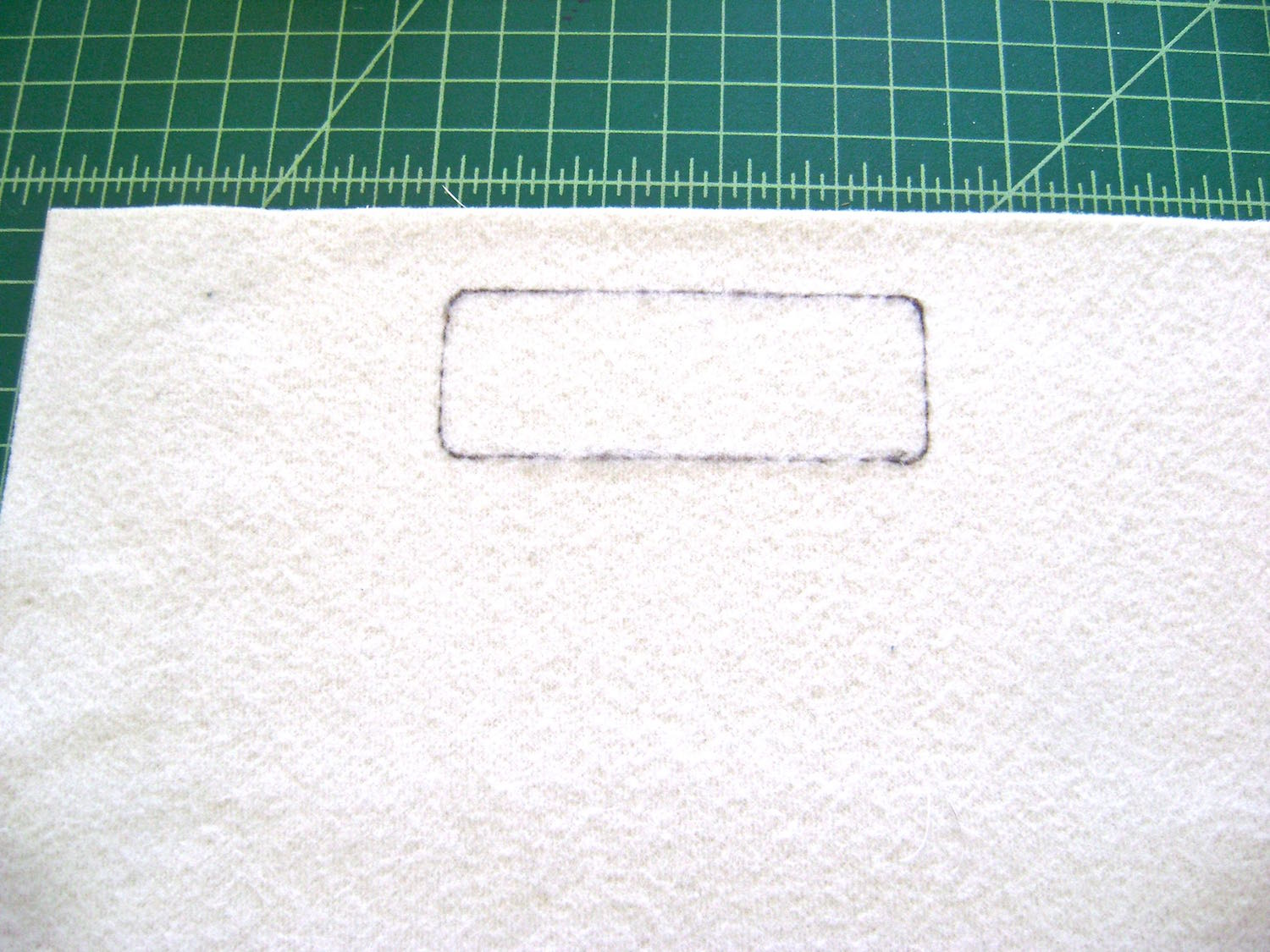 """step 6 - On the vinyl's wrong side, roughly draw the outside edges of the pattern's stitching line to determine it's placement. The pattern's stitching line should be placed 1.75"""" from the top edge of the vinyl with the centers aligned. Cover the marked area with fusible hem tape strips. Place the vinyl facing down with the top and side edges aligned to the front piece."""