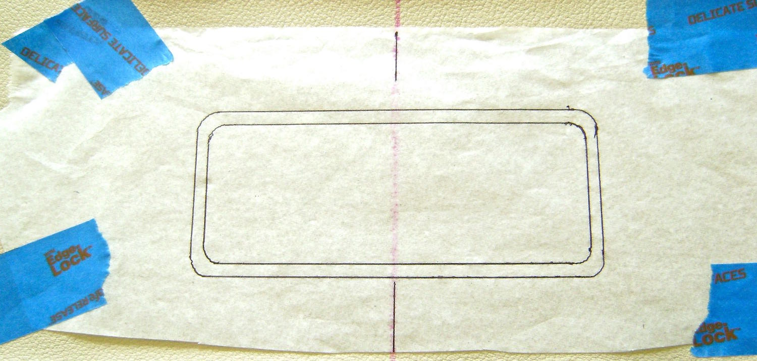 """step 8 - Place a tissue pattern on the right side of the front vinyl piece aligning the center lines and positioning the stitch line of the pattern 1.75"""" from the top edge of the vinyl. Tape the tissue borders to the vinyl with painters tape."""
