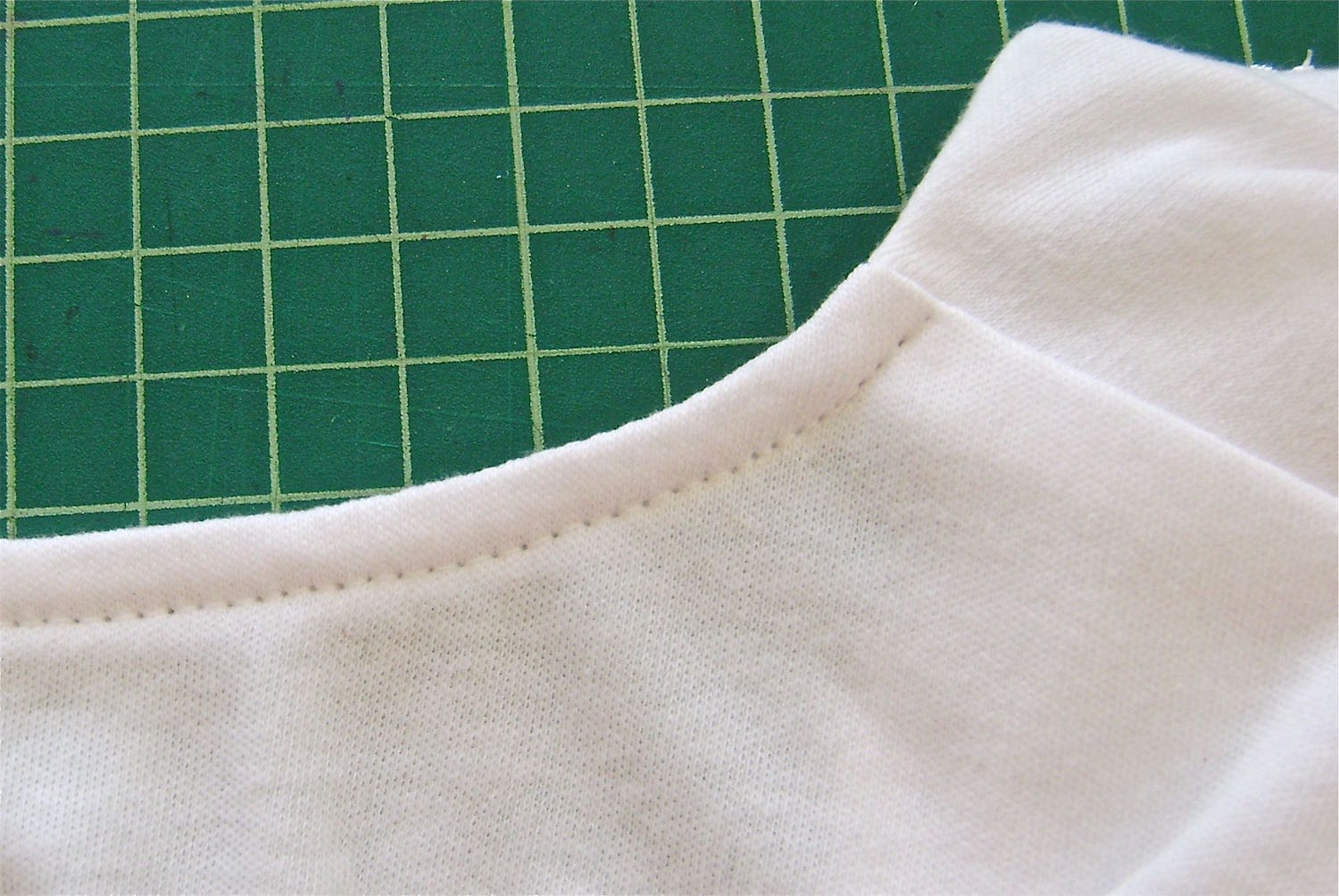 "step 16 - Use a 5/8"" seam to sew the band to the neck.  Top stitch the allowance to the band then cut away excess bulk. Turn the band to the inside of the shirt and top stitch in place close to the folded edge, from shoulder to shoulder."