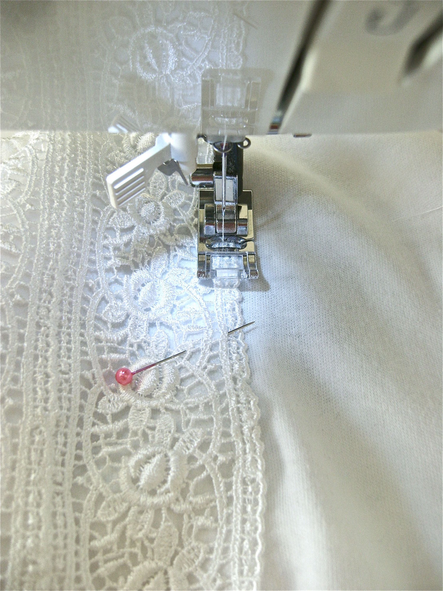 "step 17 - Turn the front facing inside the shirt.  With a regular stitch, sew the outside and bottom edges of the lace to the shirt catching the facing as you work.  Finish by sewing close to the center ""V"" to join the shirt to the lace."