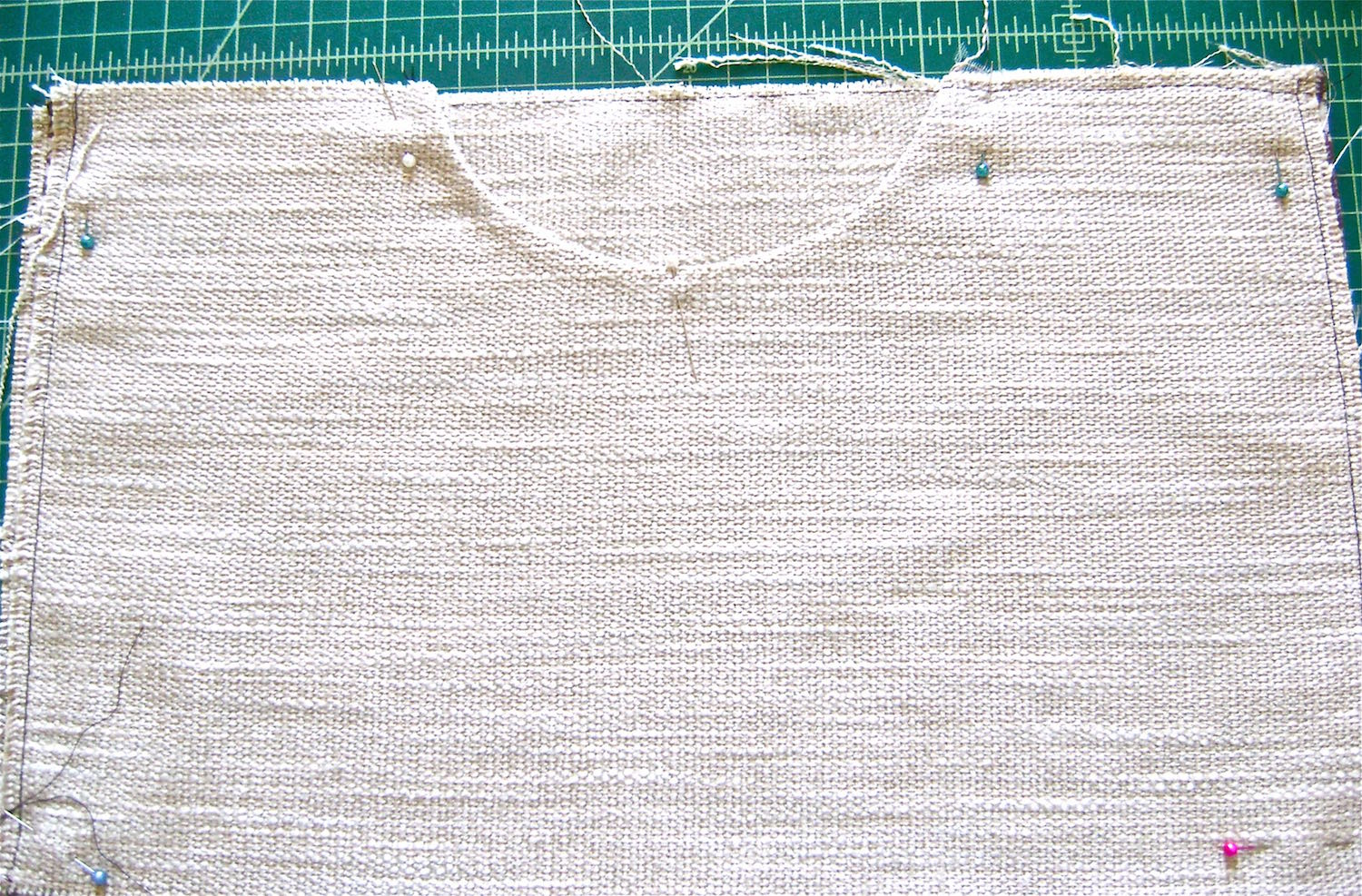 "step 2 -  Pockets   Use the template to cut out the pocket opening shape.  Sew the linings to the pocket pieces right sides together with stay tape on the 5/8"" seam line.  Topstitch seam allowance to the lining.  Trim the seam allowance.  Press with wrong sides together.  Align the top of the front pocket to the top of the woven fabric with the lining against the right side of the woven fabric.  Machine baste the top edge and sides."