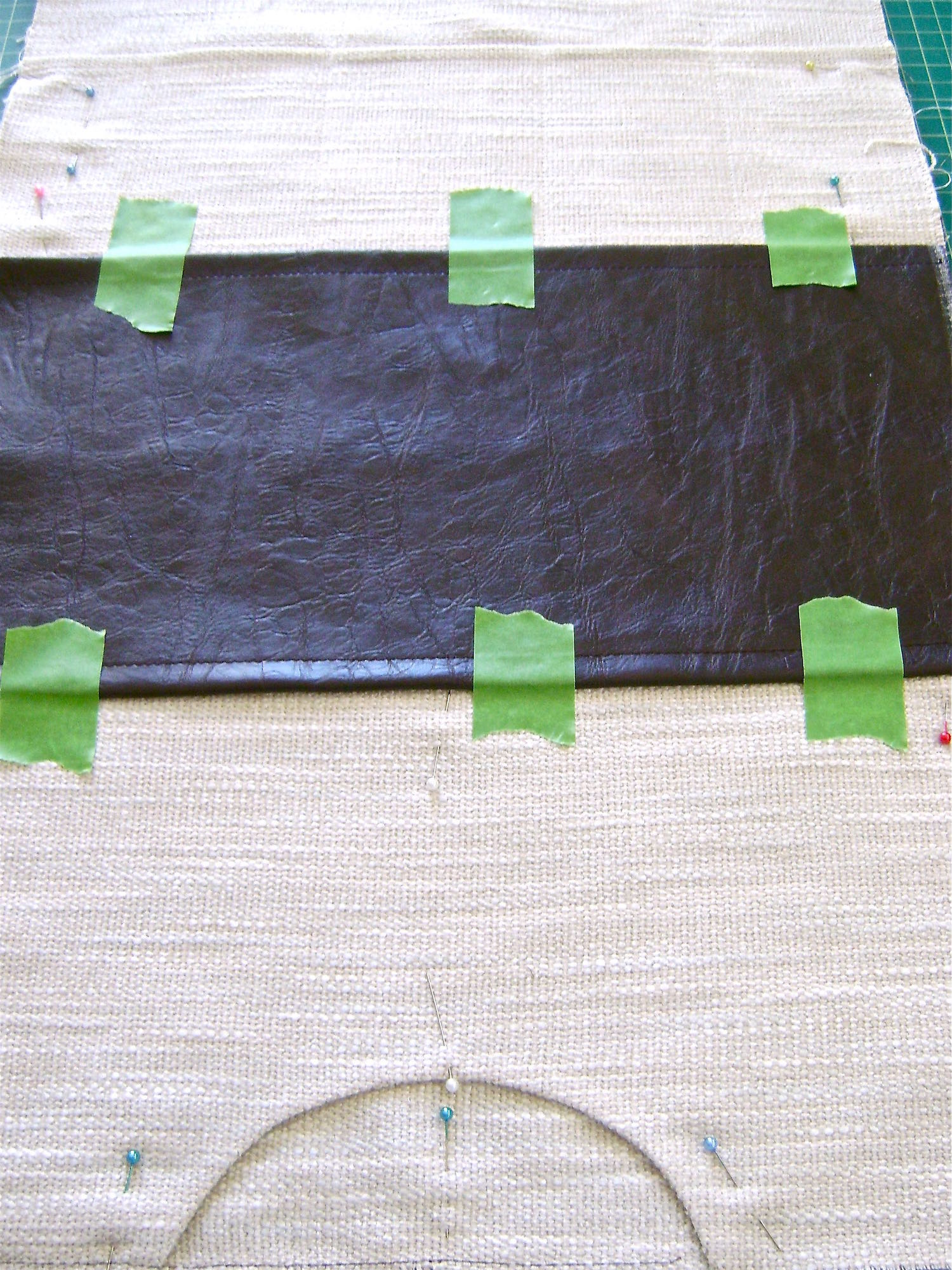 "step 4 -  Attach The Brown Bottom  With right sides together, match the top edges of the front and back of the bag.  Cut slits to mark the bottom fold which will be the bottom center of the bag.  Fold the brown vinyl for the bottom of the bag with the long ends together and mark or cut slits to indicate the bottom center of the bag. Turn a .25"" seam on both long edges of the piece and topstitch at a little less than .25"" from the edge.  Align the wrong side of the brown vinyl to the right side of the woven fabric matching up the center bottom slits.  Sew the brown edges to the woven fabric close to the existing stitch lines."