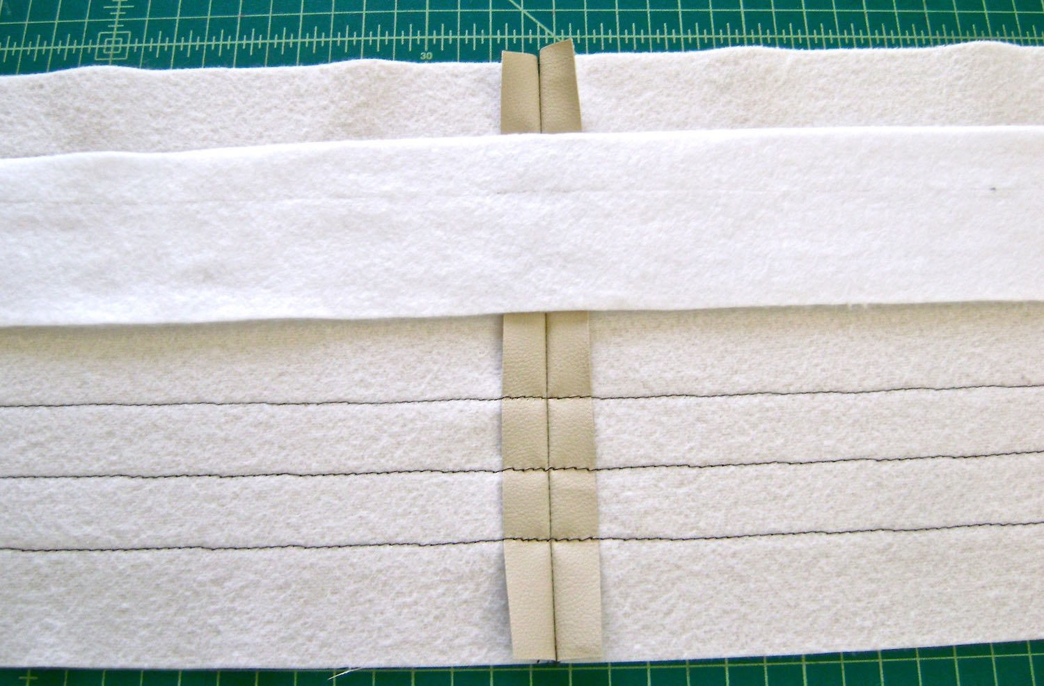 "step 6 -  Top Band   Sew the side seams with right sides together.   The decorative top stitching starts one inch from the center of the band when it's folded in half.  Use disappearing ink to create five straight lines with a ruler .50"" apart on the right side of the front and back pieces. Turn the vinyl to the wrong side and press the fusible interfacing into place.  Align the fleece with the top fold line of the band and glue or fuse in several places.  Allow to dry."