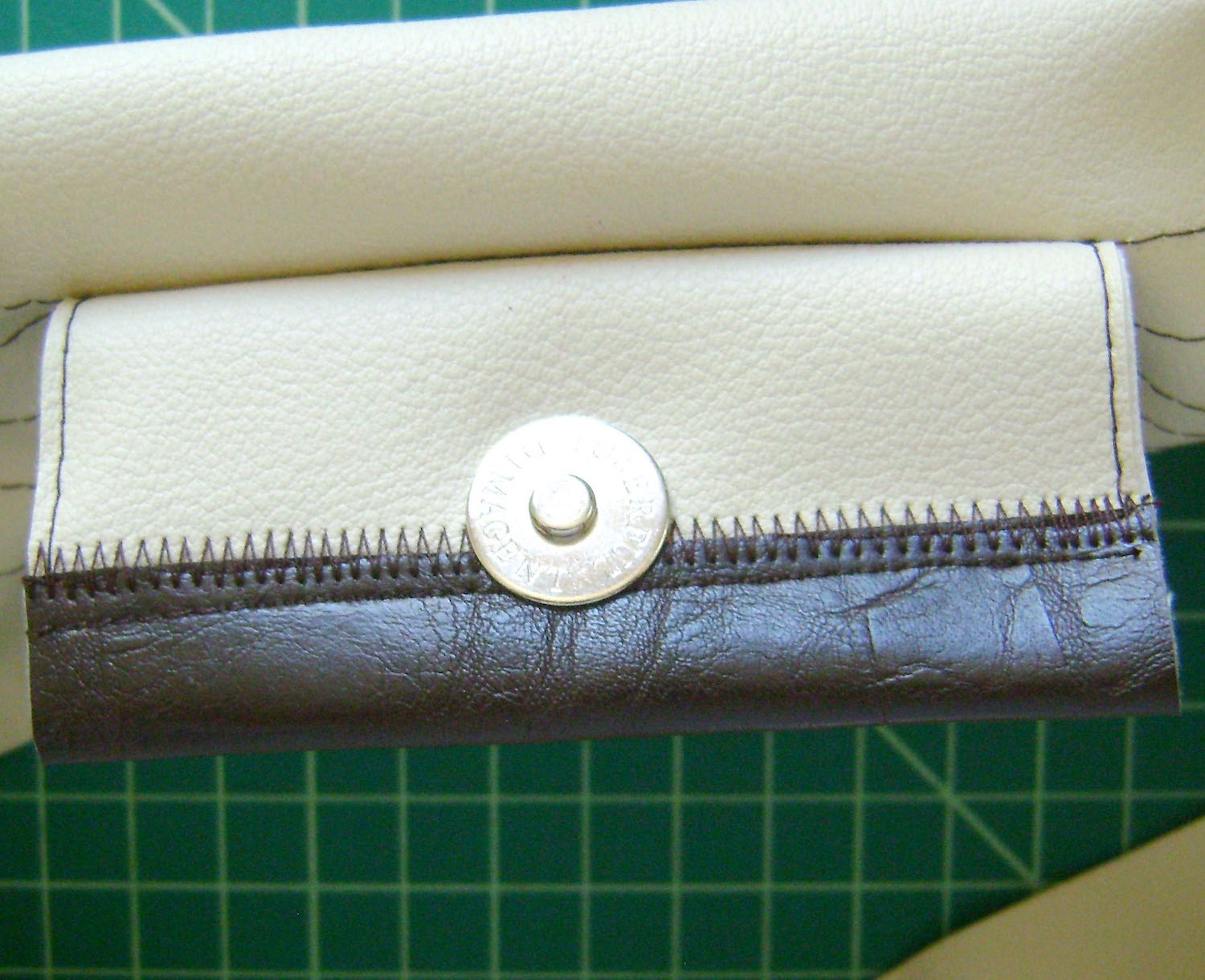 step 9 - Attach the magnetic clasp to the flap center.  Attach the matching clasp piece to the opposite side of the band reinforcing it with a piece of cardboard on the back side of the band between the front and back clasp piece.  Fold the band in half and pin the raw edges together.