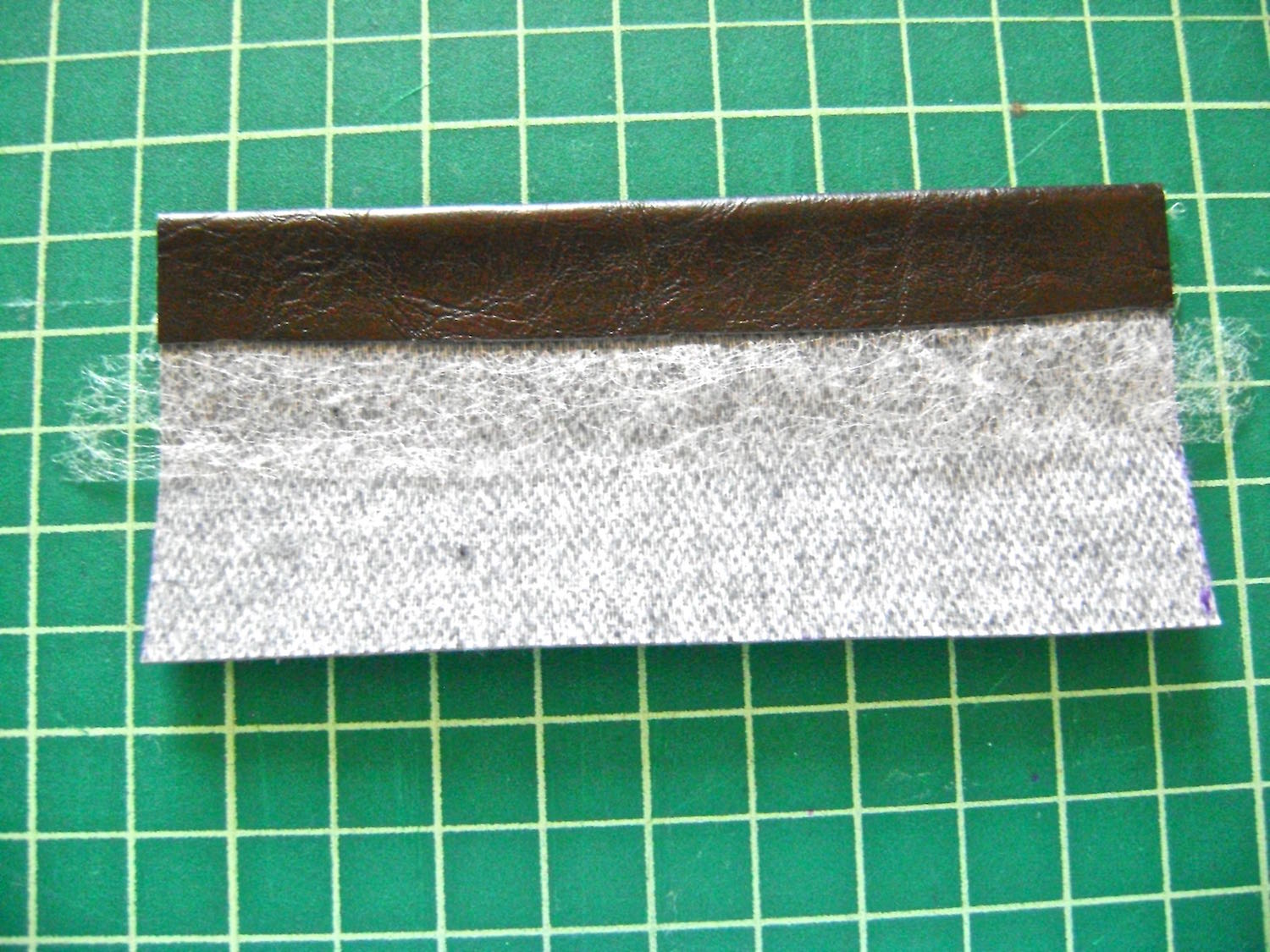 step 10 -  Strap Tabs  Center two strips of fusible tape side by side on the wrong side of the tabs.   Fold the raw edges in to meet at the center and iron the vinyl with a pressing cloth to fuse the hems in place.