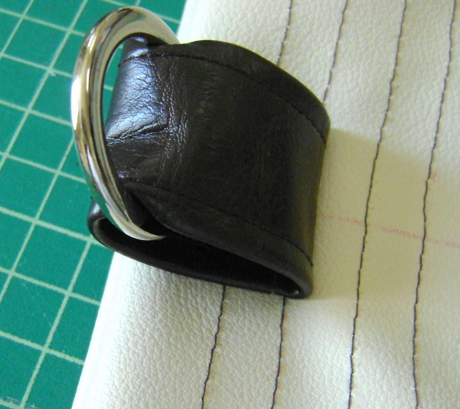 step 12 - Slide a ring onto the tab.  Turn the tab with the right side facing the right side of the band, tucking the end against the trimmed edge.  Sew the tab across the first stitching line of the band. Sew in a rectangle moving across the bottom edge and ending where you started.  Repeat for all four tabs.