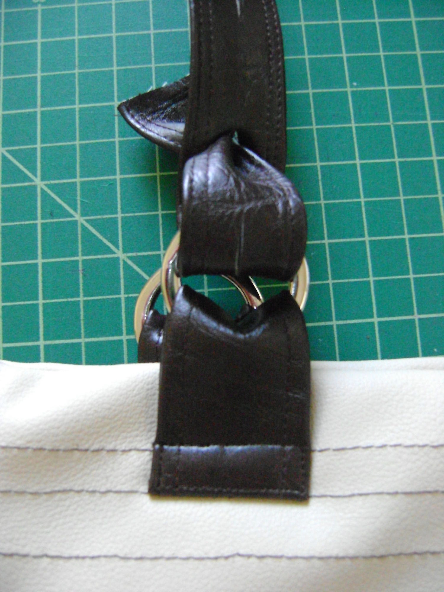 step 17 - Insert the hemmed end of the strap into the metal ring from back to front.  Bring the end of the strap through slit one.