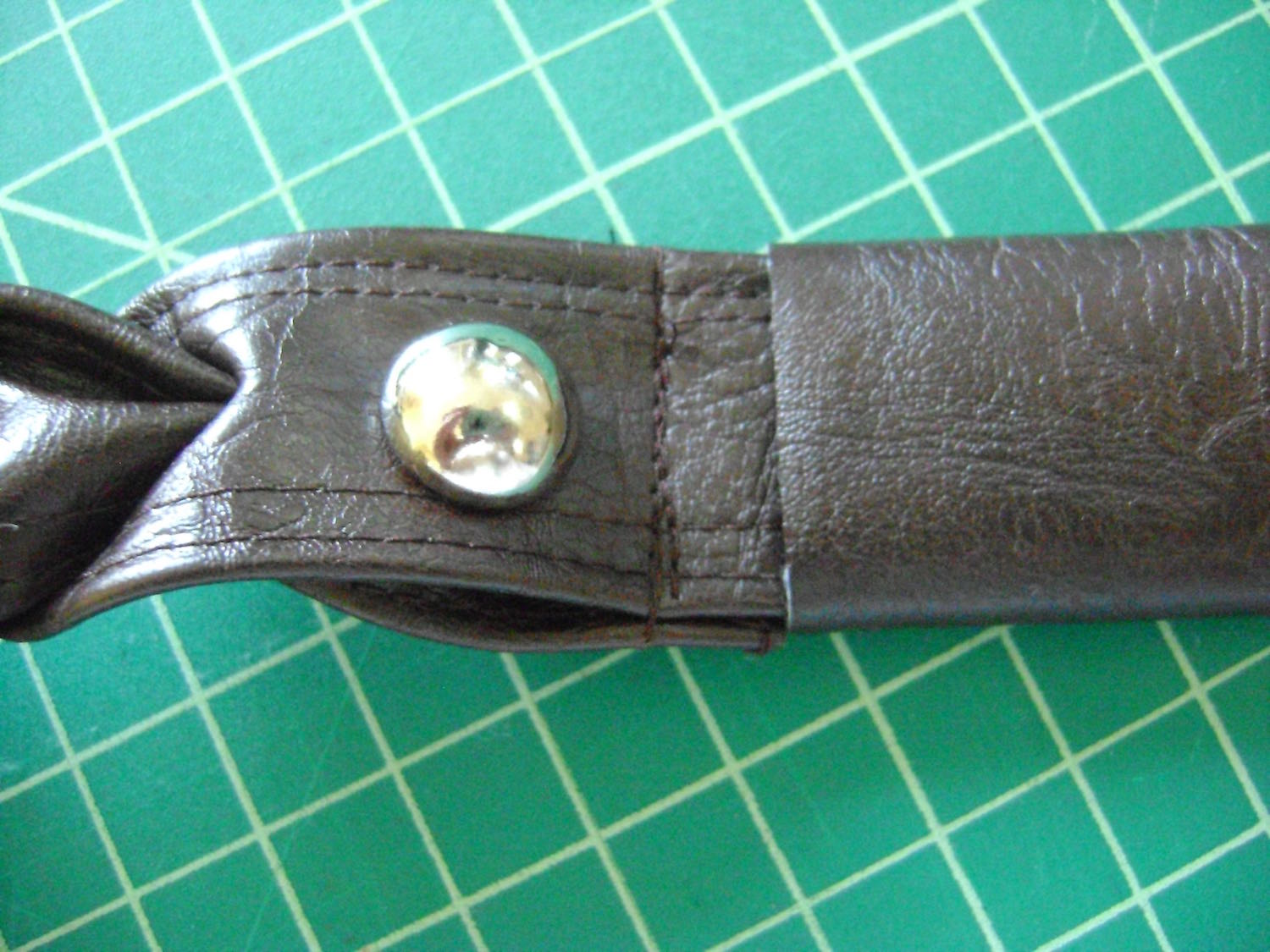 "step 19 -  Strap Covers  Fold a cover in half to measure 2"" by 4"".  Sew a .50"" seam with the right sides together.  Turn the cover right side out.  Slip it over the unfinished end of a strap and slide it close to the brad to hide the stitching that holds the two straps together.  Turn the raw edges of the covers under on both sides so the cover measures 1.50"" long.  Apply E6000 glue under the covers to keep them from sliding up the strap."