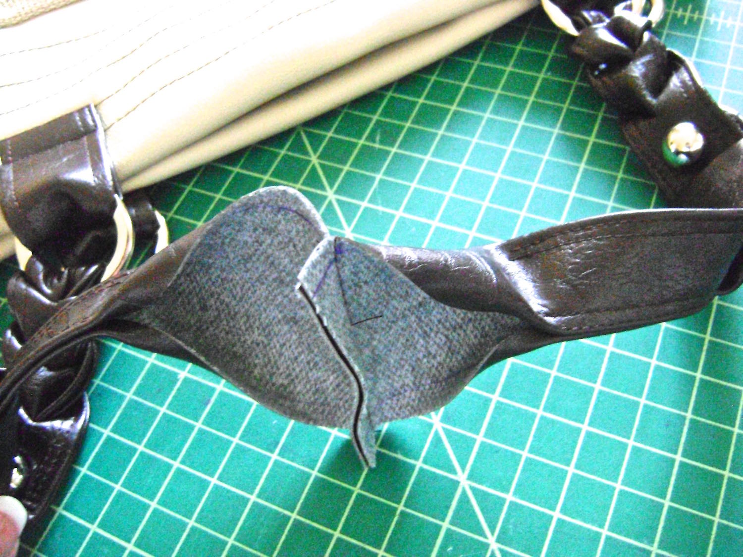 "step 20 - With right sides together, sew each set of straps with a .50"" seam to create one long strap on the the front and one on the back of the bag.  Turn the edges .50"" to finish hemming the strap with top stitching.  Add a .25"" brad to teach of the strap tabs."