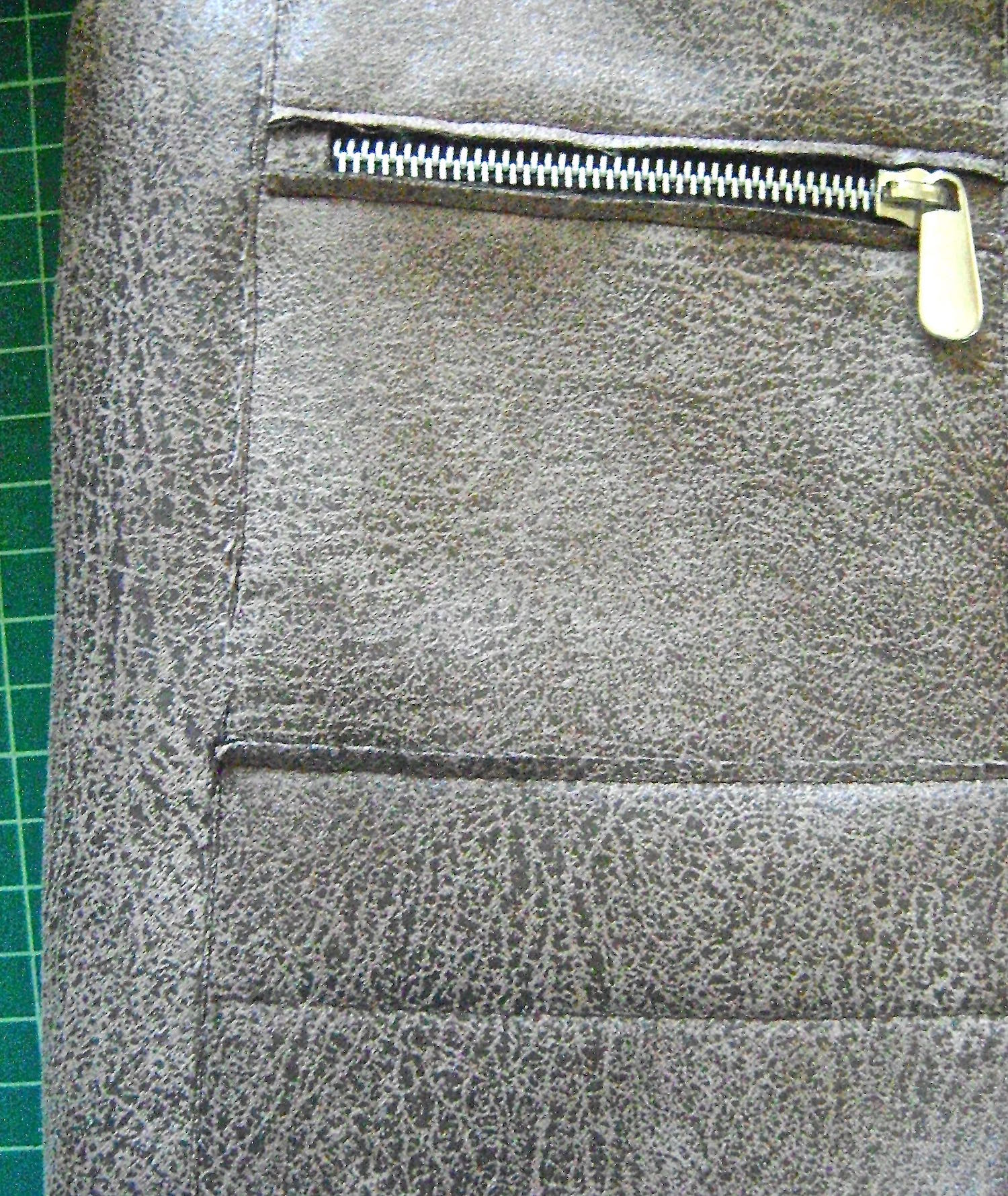 """step 17 - Topstitch a continuous vertical line from the top outside edges of the zippered pockets to the bottom of the lower pockets 1/8"""" from the raw edges."""