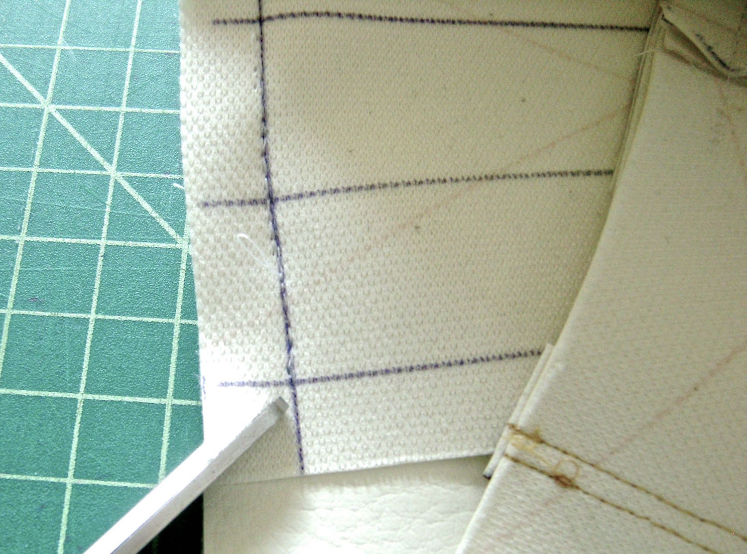 "step 6 -    Bottom  On the wrong side of the center bottom piece, draw lines .50"" from all edges and a line down the center.  Make a small slit less than 1/2"" on the front and back purse pieces 1"" away from each side seam.  Stitch the center purse bottom to the sides then the front and back with right sides together.  Cut a diagonal slit in the corners of the bottom piece.  Pivot the stitch at the slits to create clean, square corners."