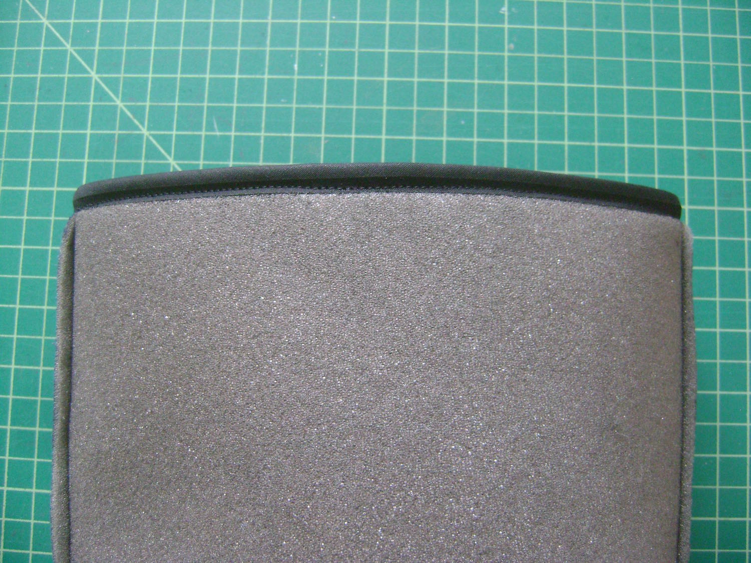 "step 9 - Cut a piece of bias tape to measure 21"".  Sew the ends together.  Encase the top edge of the headliner with bias tape by sewing one edge to the top of the headliner, then folding it over and top stitching the other edge."