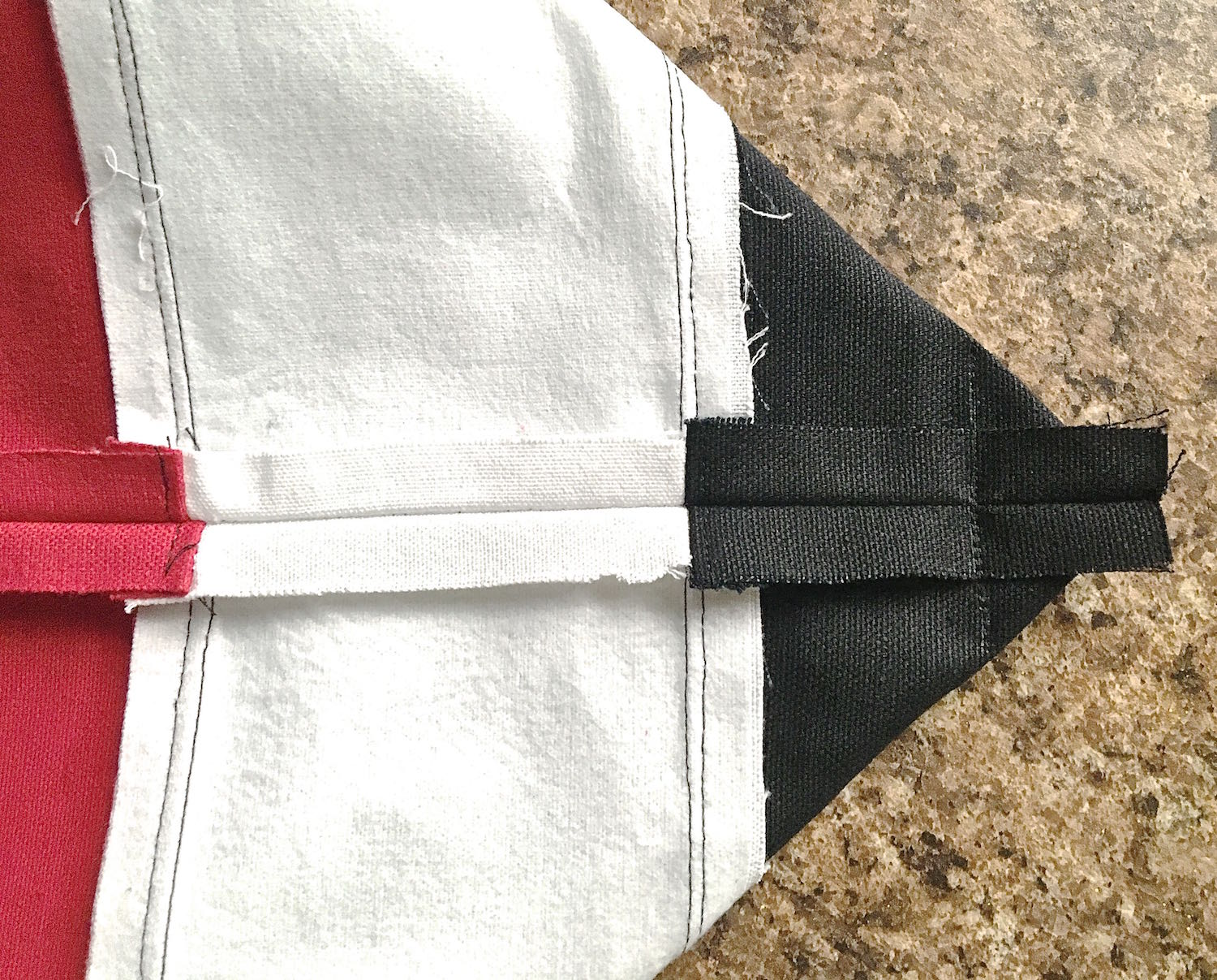 """step 7 -  Facing  To create the bag bottom, align the side seam with the center bottom of the bag and press it flat with your hands. Draw a line across the fabric2"""" from the point. There should be 1"""" to the left and right of the seam. Stitch across the line. Repeat this on the other side of the bag."""