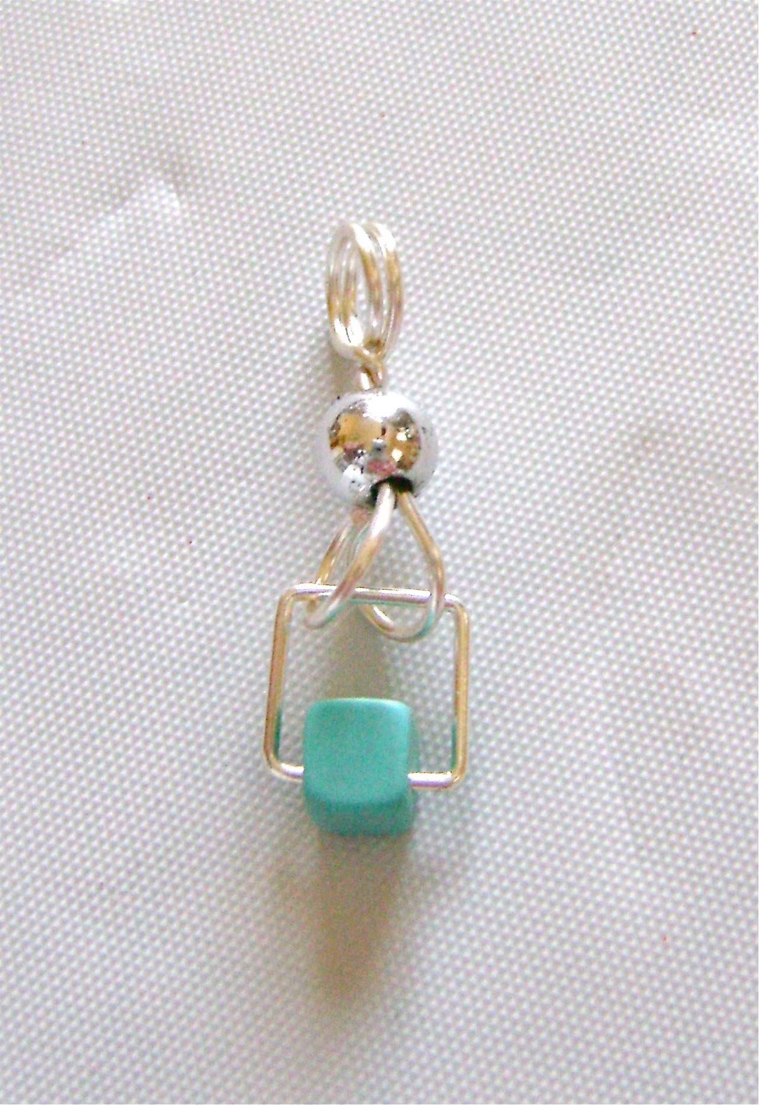 step 8 - Arranging the loops so that each one is slanted outward to the corners of the square will keep the square level and prevent it from rotating as you wear them. Attach an earring wire.