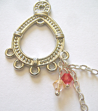 "step 4 - Open a 5mm jump ring and attach the loop of the red bead, a .75"" length of chain followed by a .50"" length of chain.  Attach the jump ring to the loop in the teardrop.  Do this four more times to fill the teardrop."
